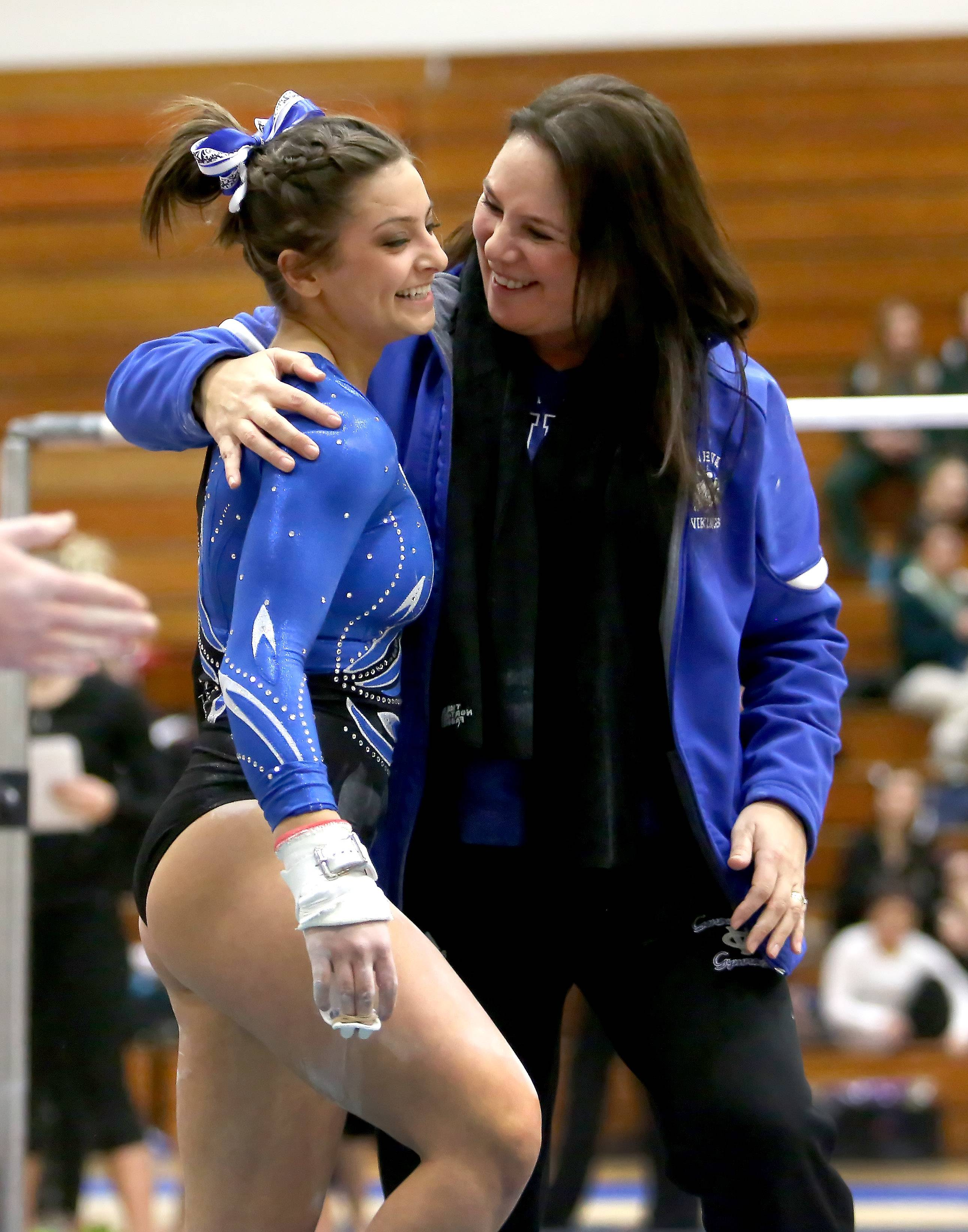 Geneva coach Kim Hostman congratulates Dominique Brognia after her uneven parallel bars routine during gymnastics sectional at Wheaton Warrenville South on Tuesday in Wheaton.