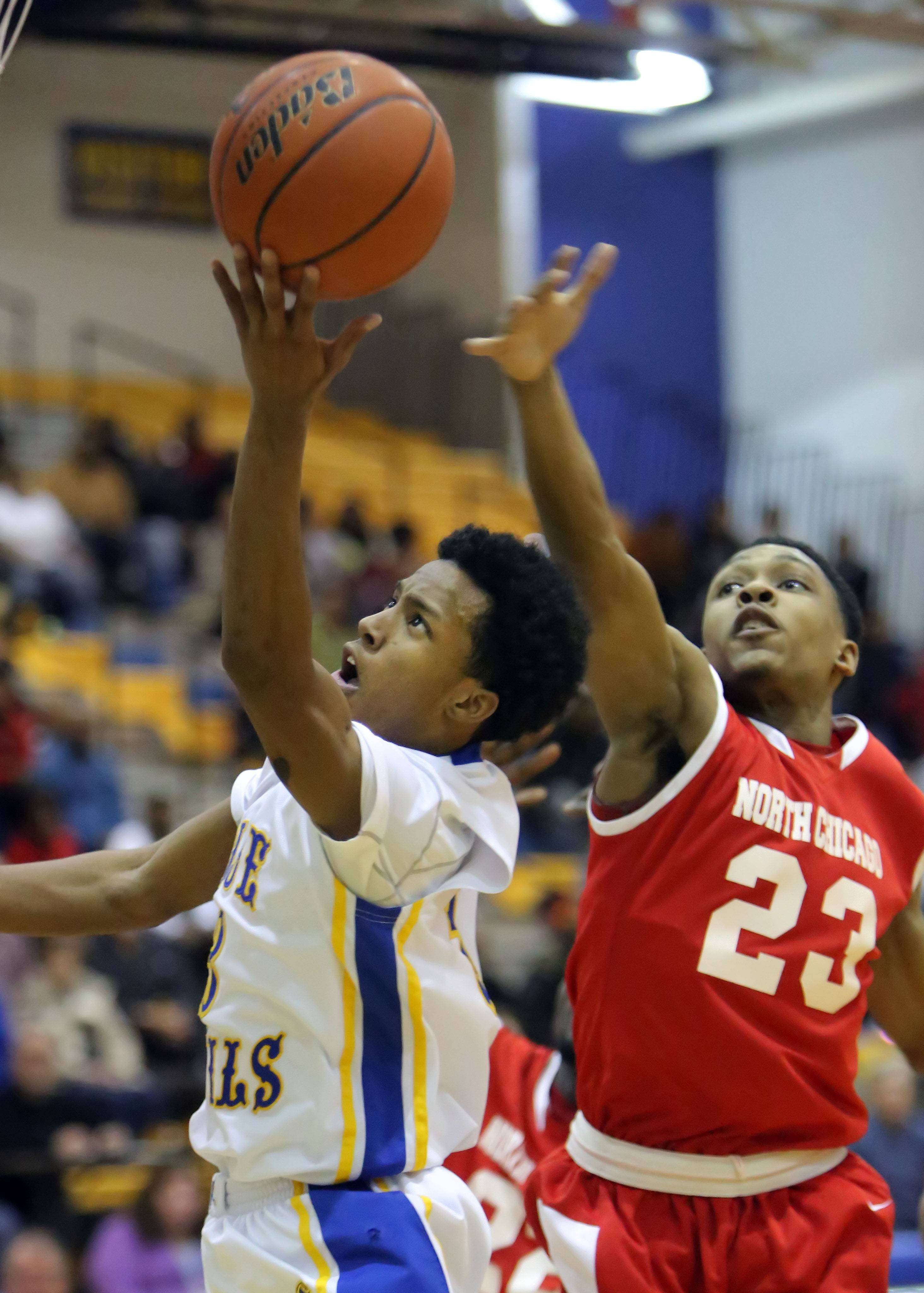 Warren's Eric Gillespie, left, drives past North Chicago's Jamero Shelton on Tuesday night at Warren.