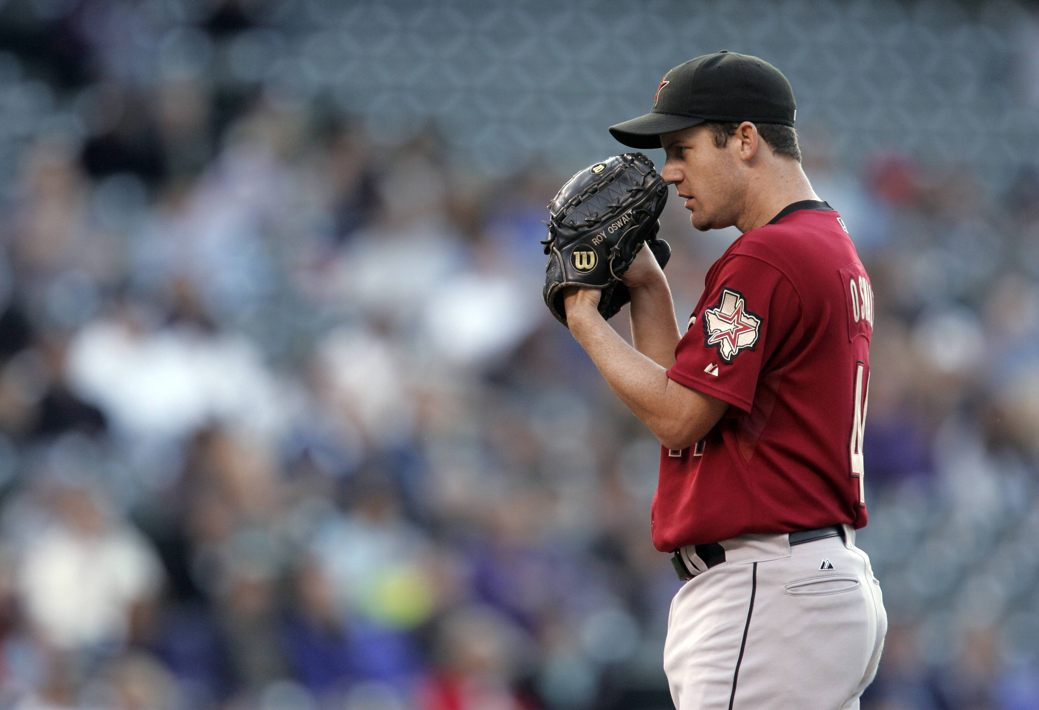 In this Sept. 6, 2008, photo, Houston Astros starting pitcher Roy Oswalt prepares to throw to a Colorado Rockies batter during a baseball game in Denver. Oswalt is retiring after 13 major league seasons. Oswalt's agent, Bob Garber, confirmed Oswalt's retirement Tuesday, Feb. 11, 2014, and said the pitcher would come to work for his agency. Oswalt, 36, had a 163-102 career record with a 3.36 ERA. His best season came with Houston in 2004, when he went 20-10 with a 3.49 ERA. (AP Photo/Jack Dempsey)