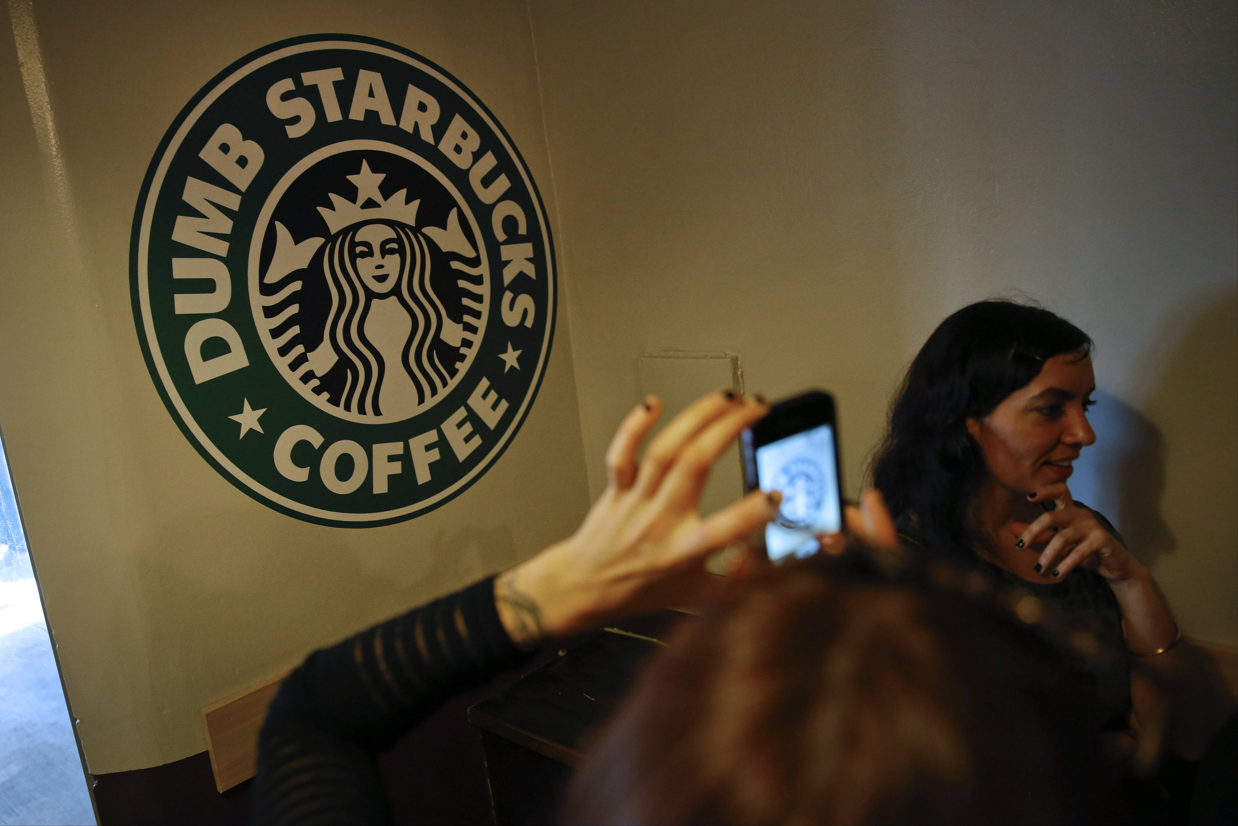 A customer photographs the Dumb Starbucks Coffee store, a parody of the Starbucks Corp. coffee chain, in Los Angeles on Monday. Dumb Starbucks, which opened this past weekend, offered Dumb Vanilla Blonde Roast, Dumb Chai Tea Latte and Dumb Caramel Macchiato, all available in sizes Dumb Venti, Dumb Grande, and Dumb Tall.