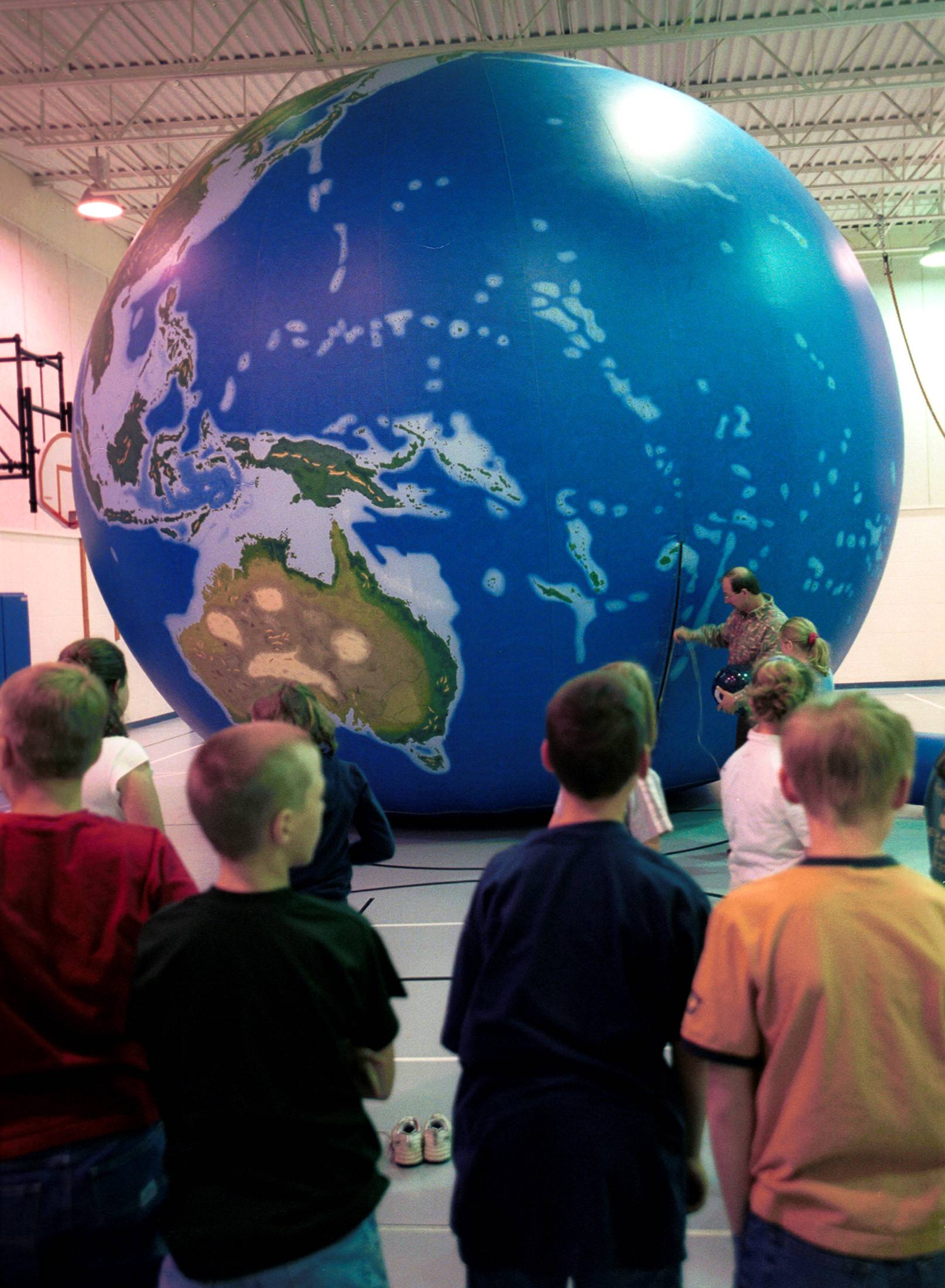 Students learn about the earth with a 20-foot-tall balloon. At this size, it's easy to see the spherical shape of the planet, but the full-size planet can look flat when you're standing on its surface.