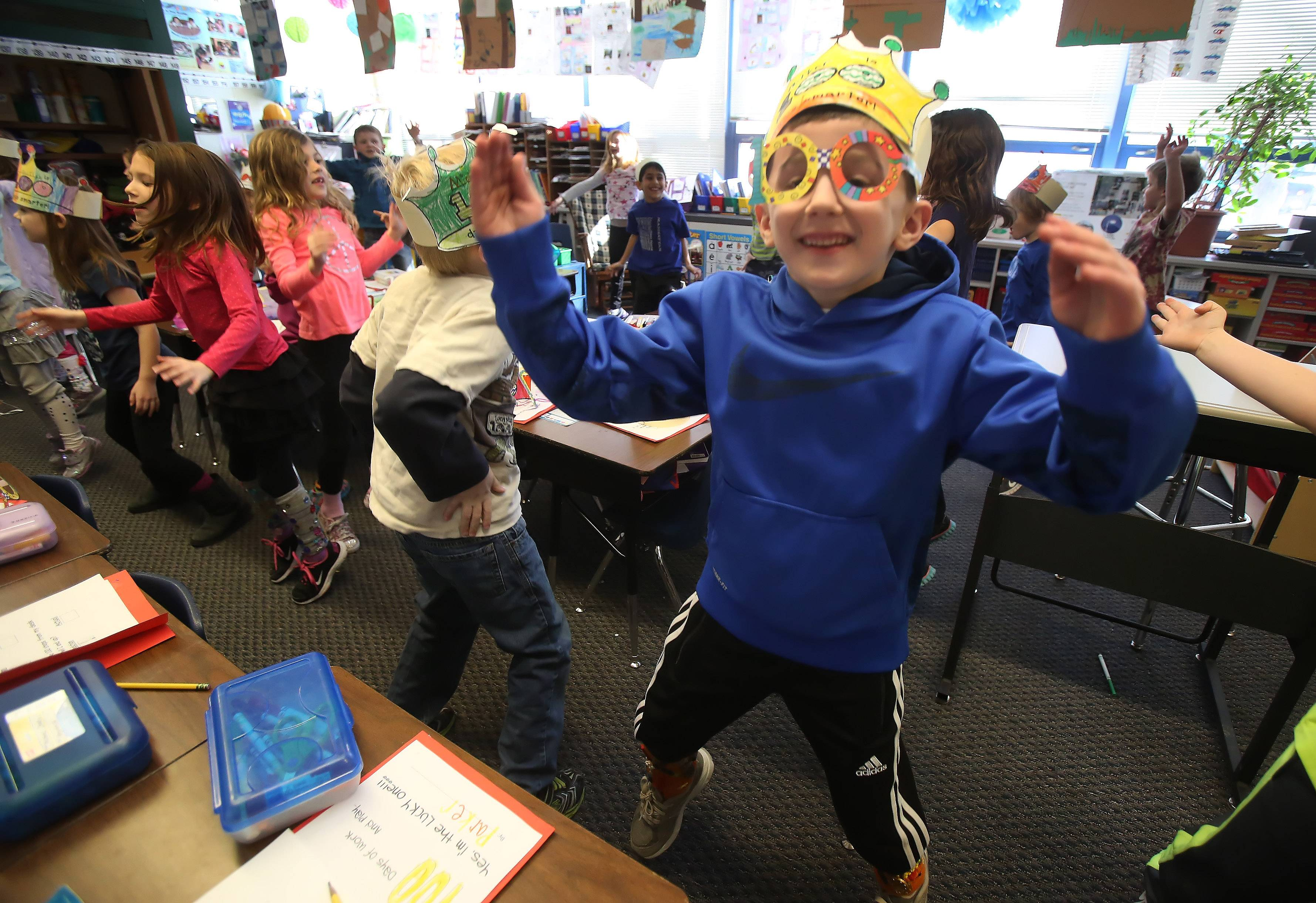 Parker Swearingin, right, joins other first grade students in counting jumping jacks during 100 seconds as they celebrate 100 days of school Tuesday at Copeland Manor School in Libertyville. The students participated in various activities involving 100, including games, exercises, writing and art projects.