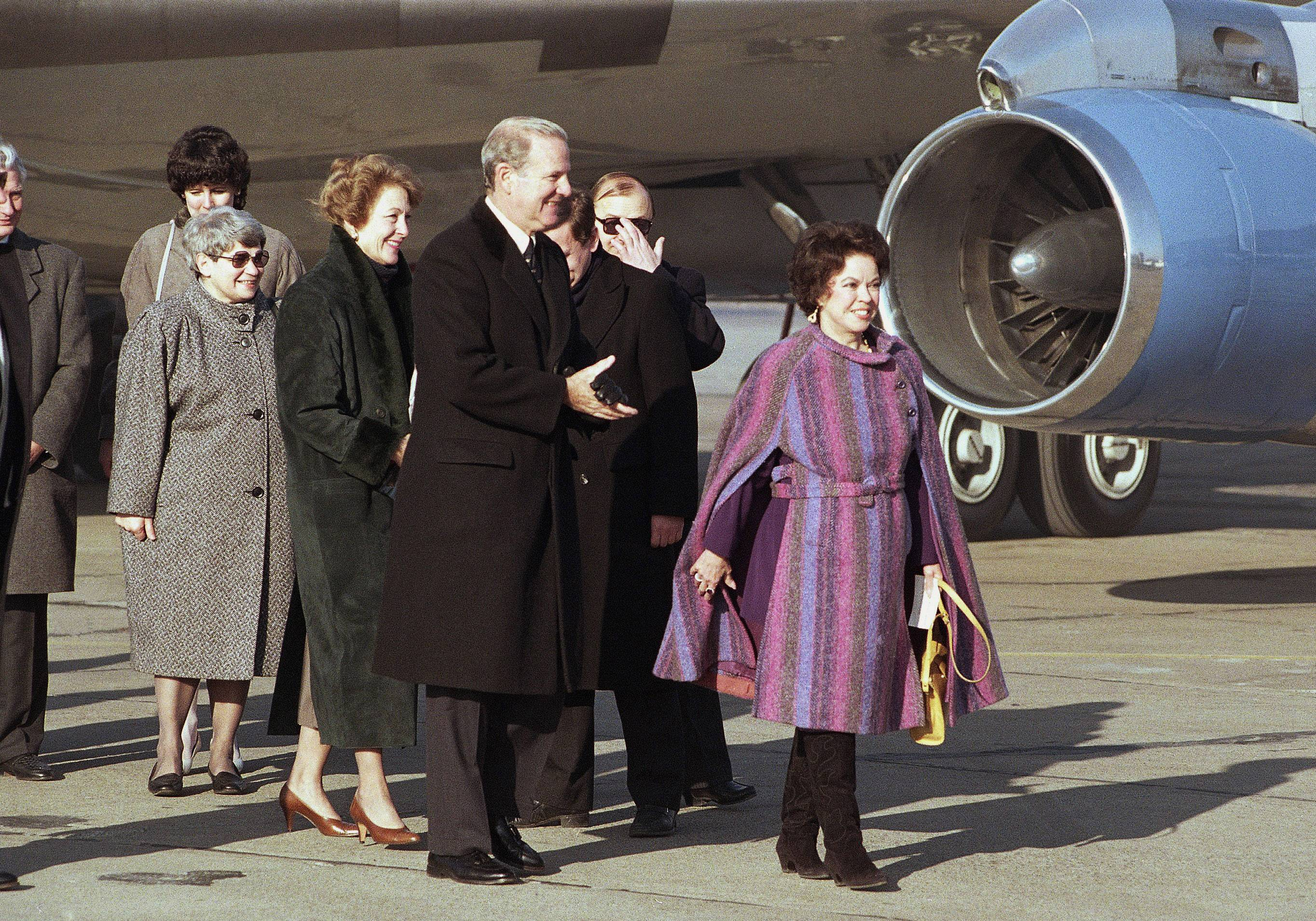 In this Tuesday, Feb. 6, 1990, file photo, U.S. Ambassador to Czechoslovakia Shirley Temple Black, right, leads U.S. Secretary of State James Baker and wife Susan from the plane at Prague Airport, in Prague.