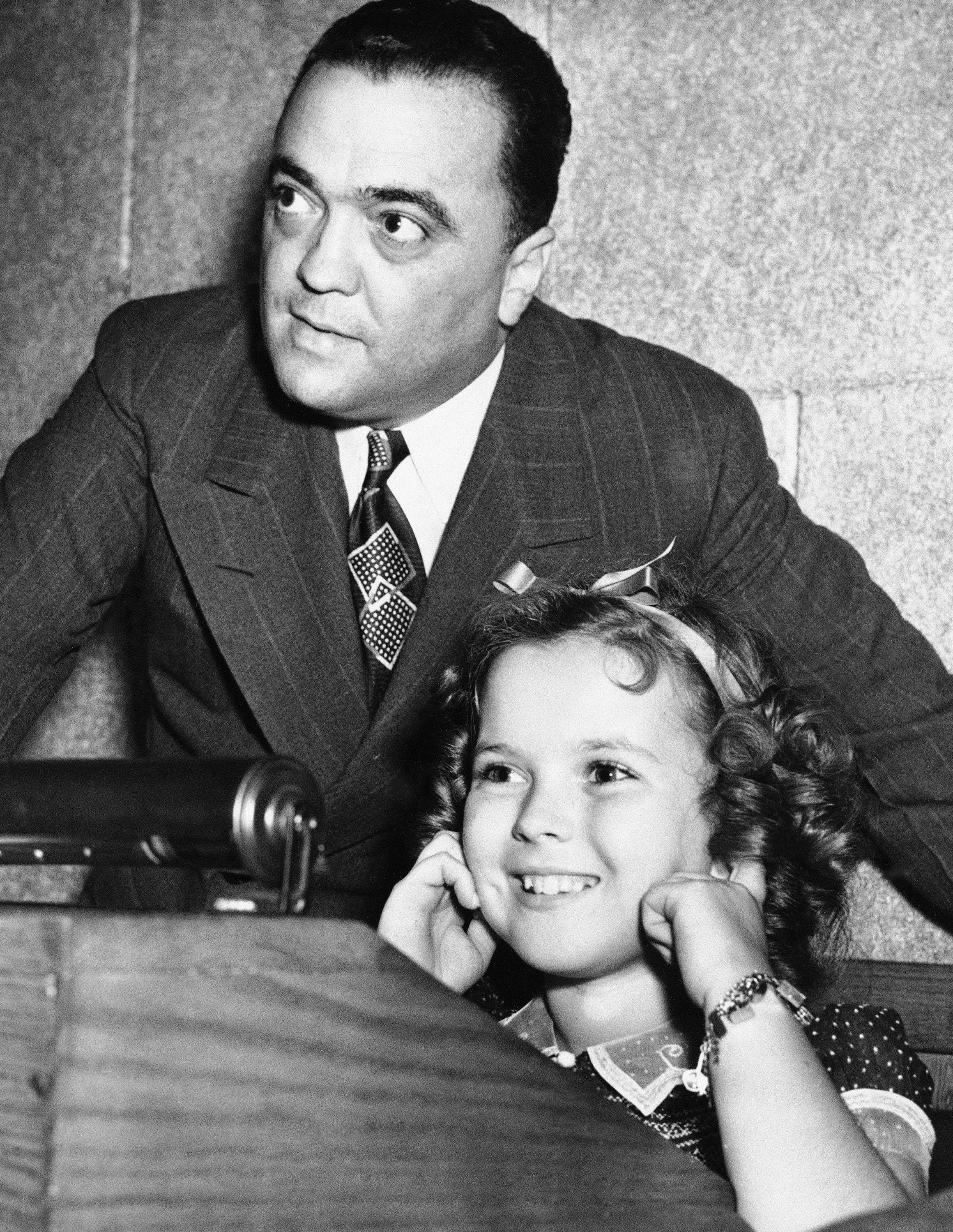 In this June 24, 1938, file photo, young actress Shirley Temple plugs her ears as her father shoots a federal agent's gun, while Federal Bureau of Investigation Director J. Edgar Hoover gives her a tour of FBI headquarters in Washington.