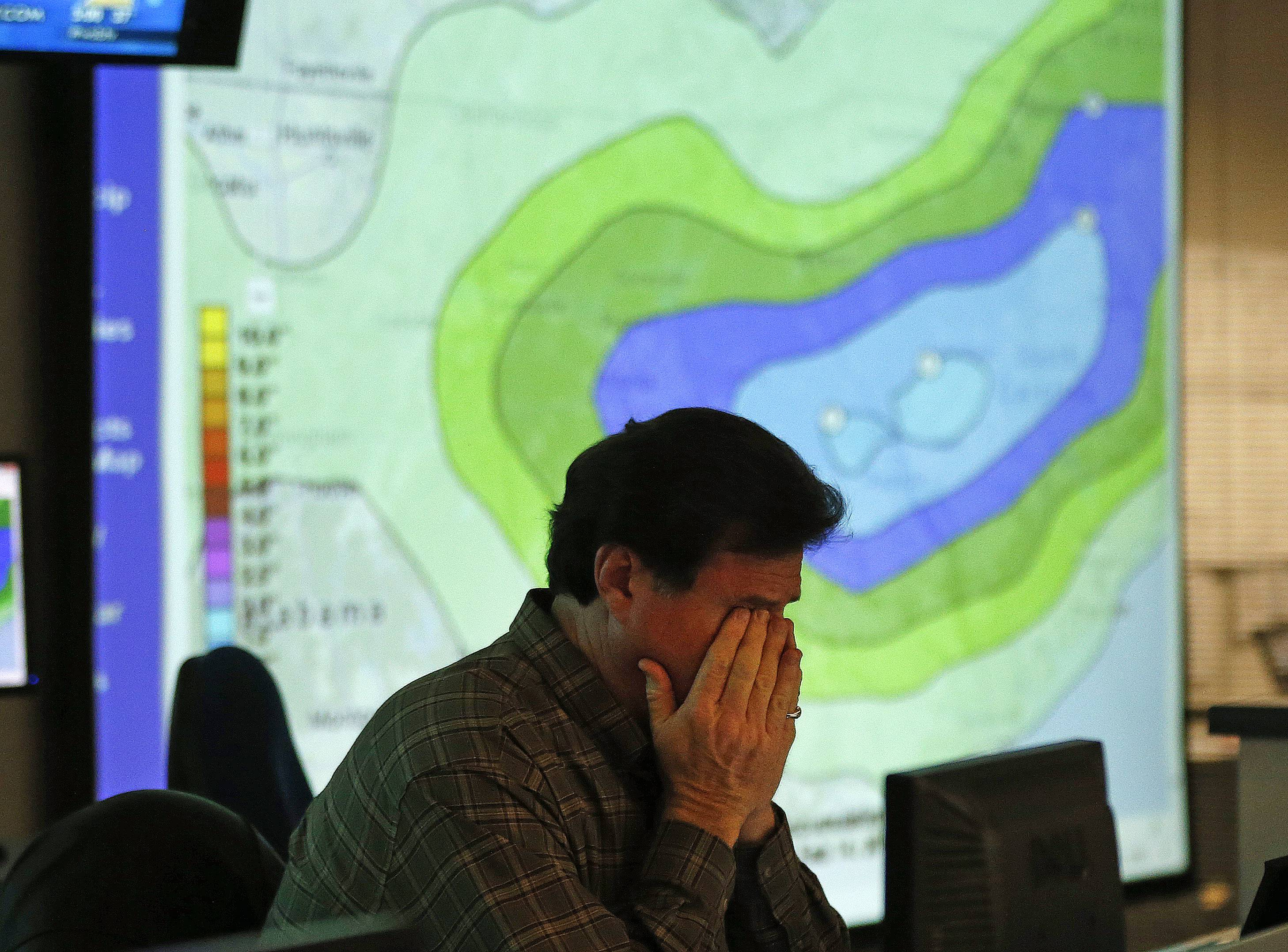 "Chuck Ray director of field operations for the Georgia Emergency Management Agency, rubs his eyes as he works in the emergency operations center Tuesday in Atlanta. Georgia is bracing for a ""catastrophic"" winter storm."