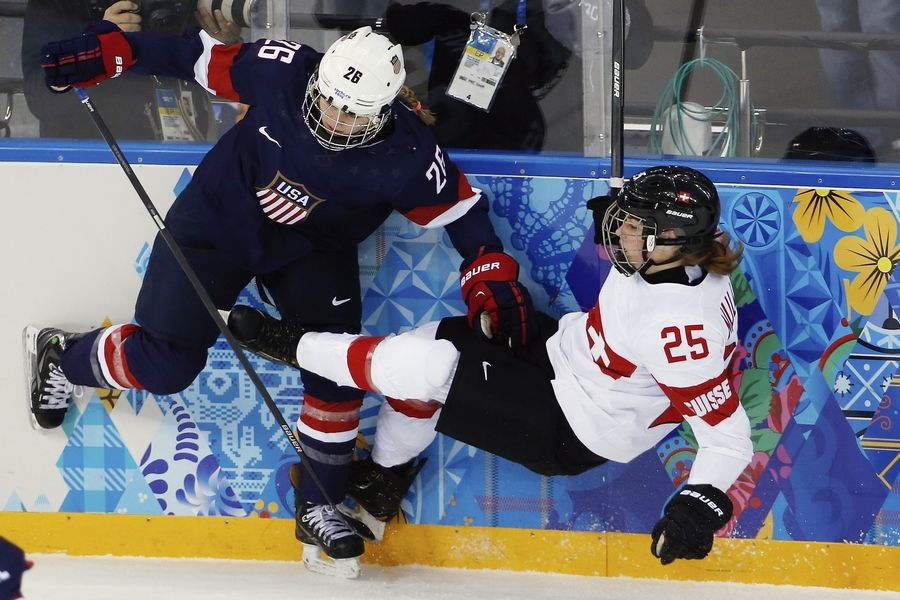 Palos Heights native Kendall Coyne of Team USA collides with Alina Muller of Switzerland against the boards during the first period of a women's ice hockey game Monday in Sochi, Russia.