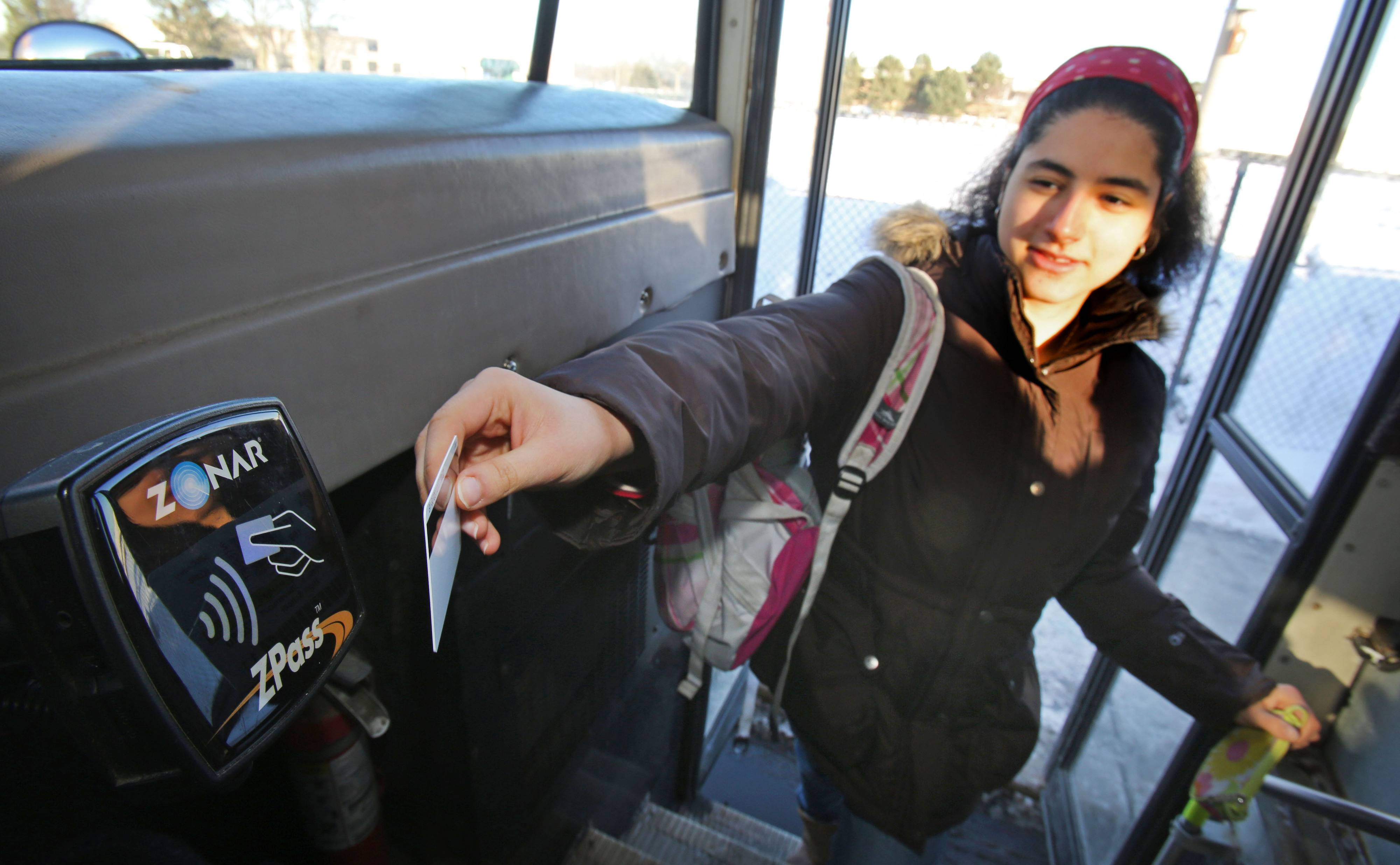 Seventeen-year-old Nilufar Jalali of Vernon Hills swipes her school ID card on ZPass scanner as she gets on the bus at Stevenson High School in Lincolnshire Monday.
