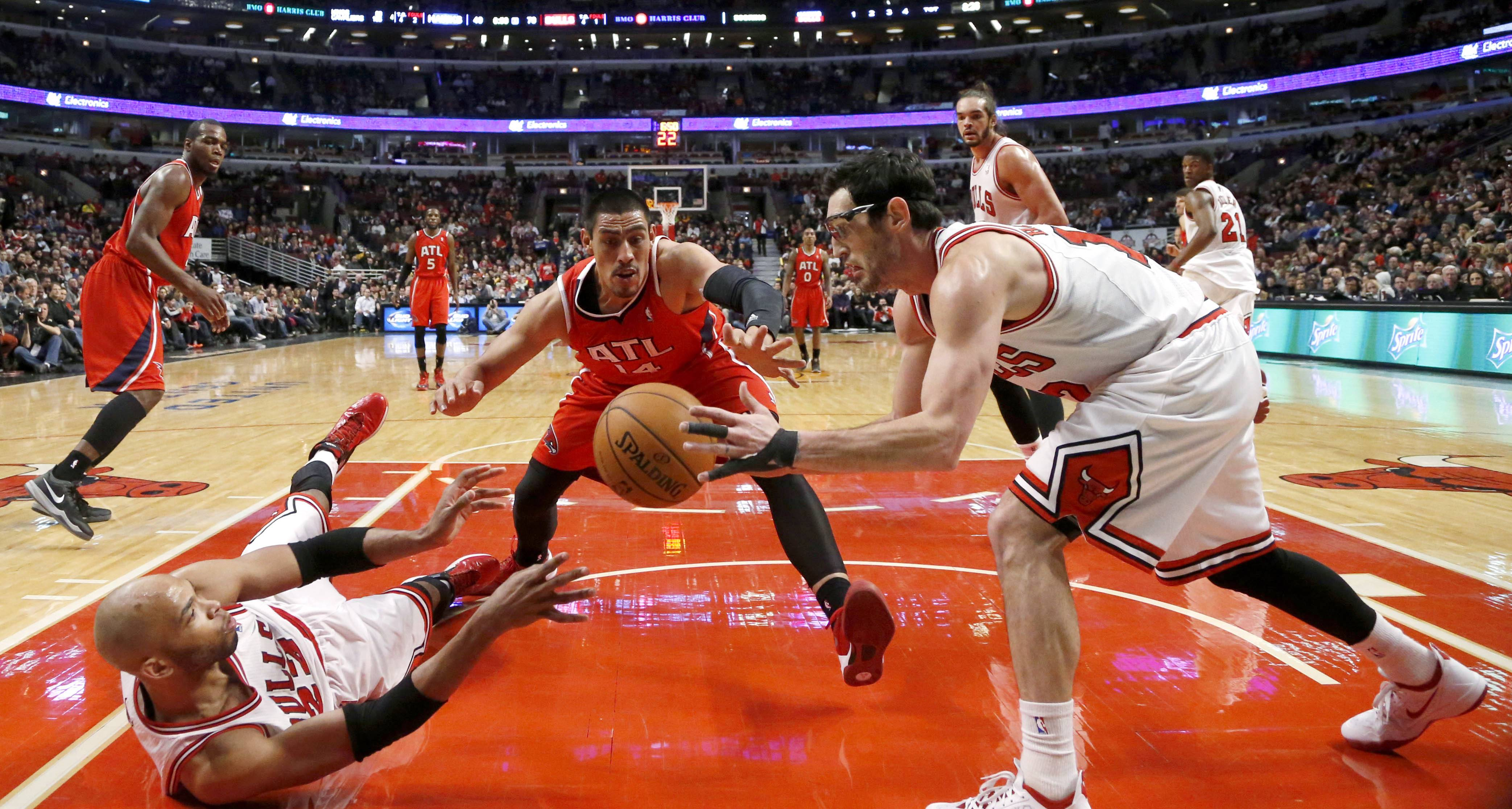 The Bulls' Taj Gibson, left, passes the ball to Kirk Hinrich as the Hawks Gustavo Ayon goes for the steal Tuesday night at the United Center.