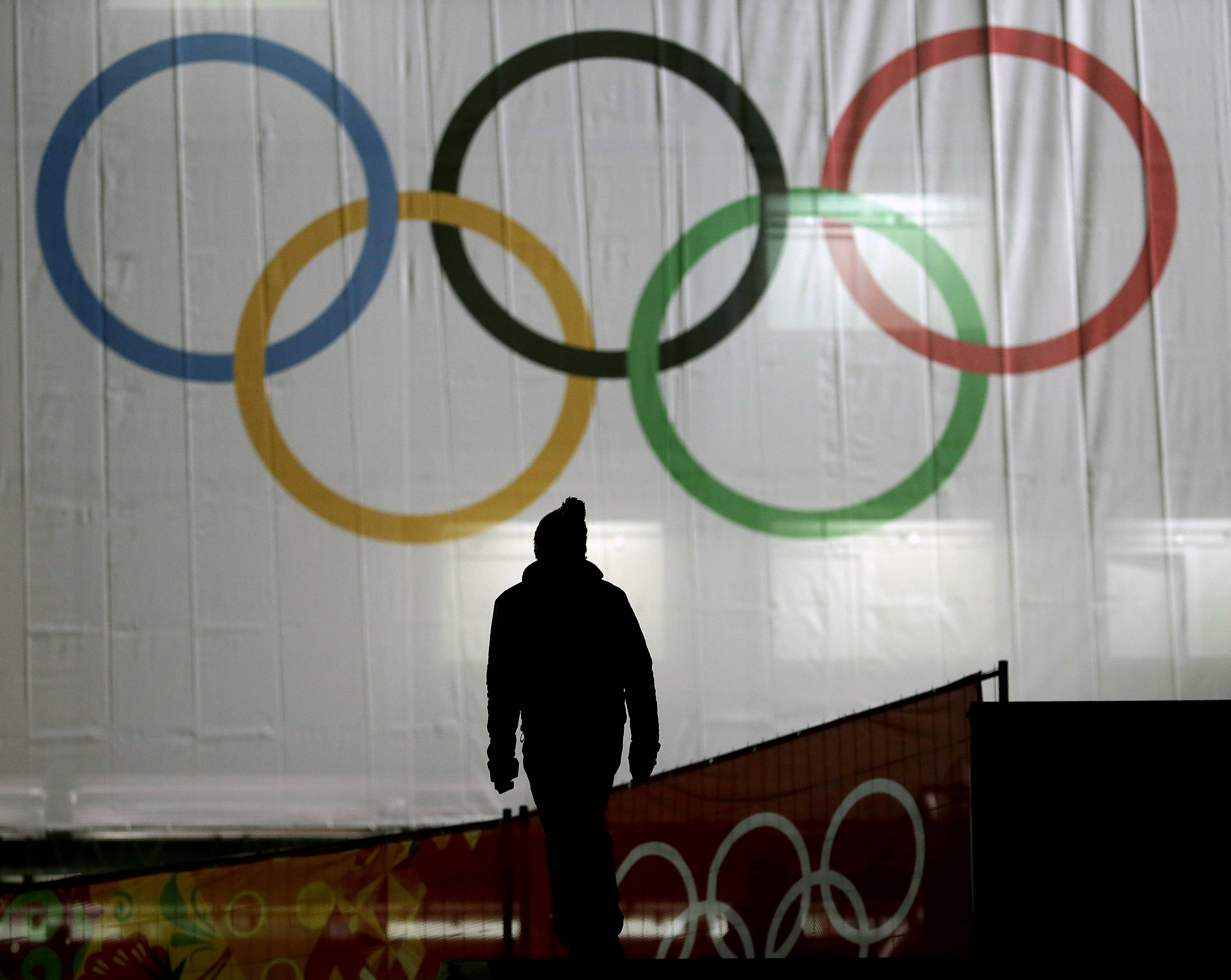A man is silhouetted against the Olympic Rings as he walks to the venue for the women's normal hill ski jumping final at the 2014 Winter Olympics on Tuesday in Krasnaya Polyana, Russia.