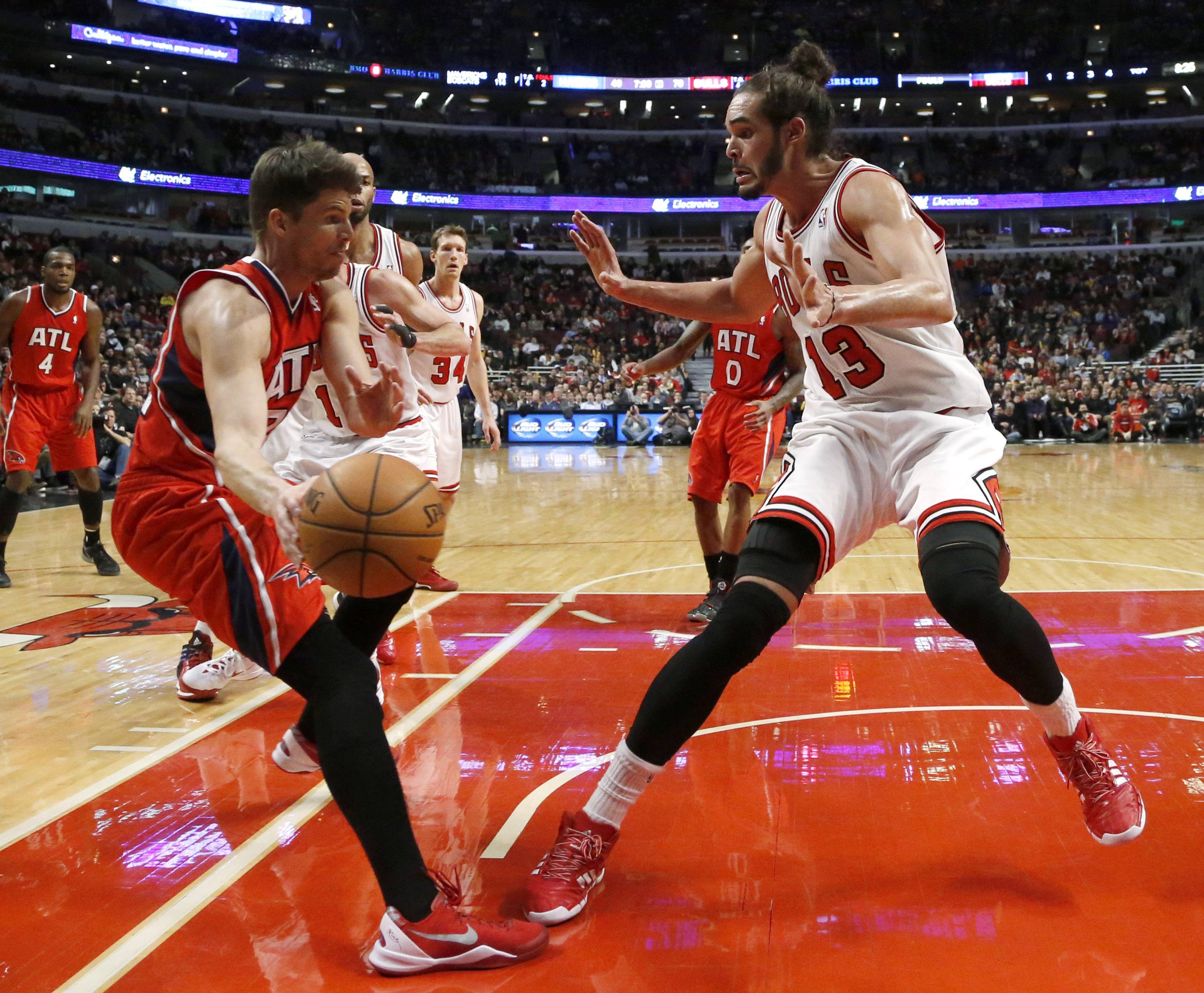 Atlanta Hawks guard Kyle Korver, left, is forced to pass as Chicago Bulls center Joakim Noah (13) defends during the second half of an NBA basketball game Tuesday, Feb. 11, 2014, in Chicago. The Bulls won 100-85.