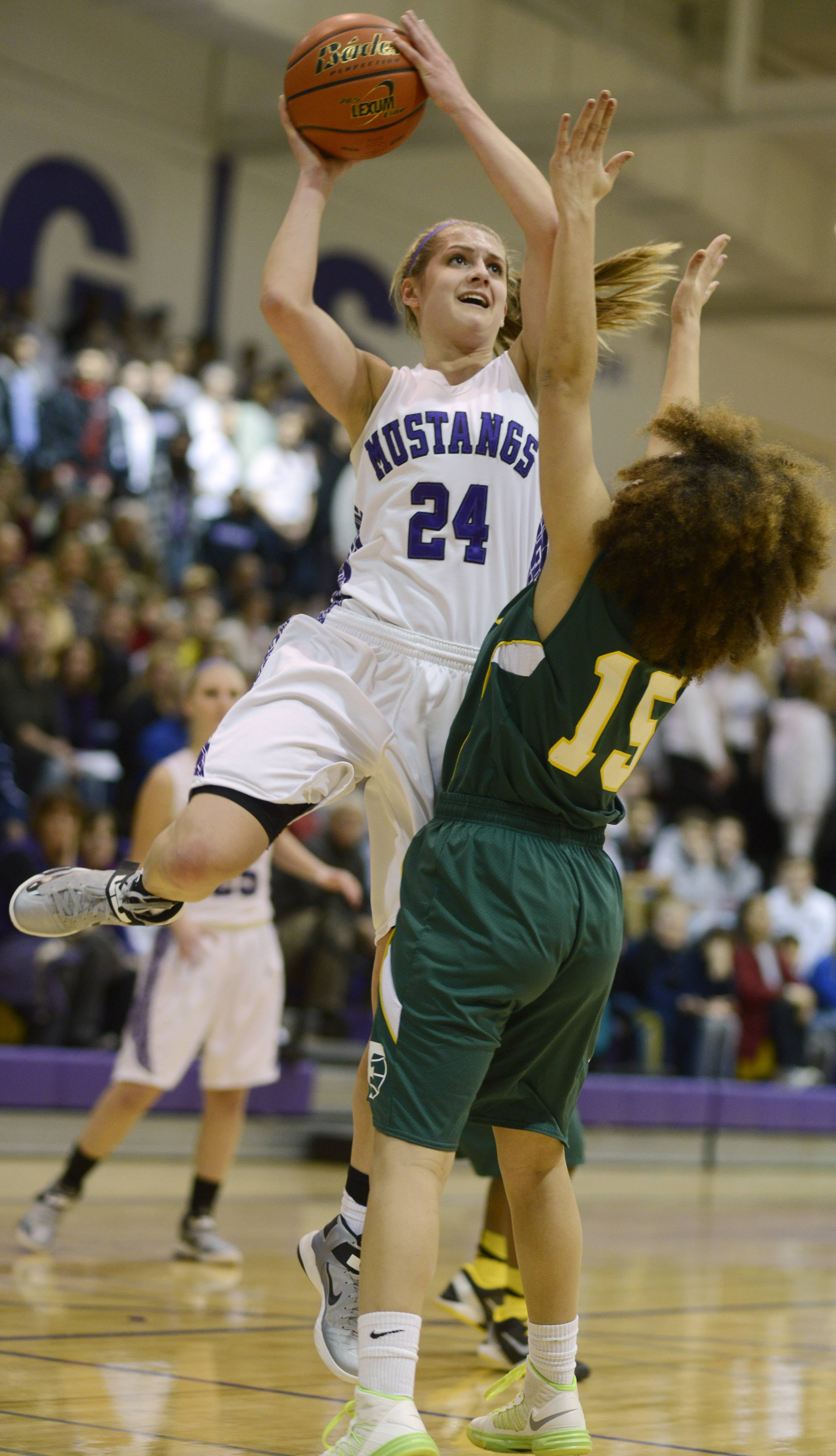 Rolling Meadows' Alexis Glasgow, left, takes a shot in front of Fremd defender Bernie Williams during last season's Mid-Suburban League championship game.