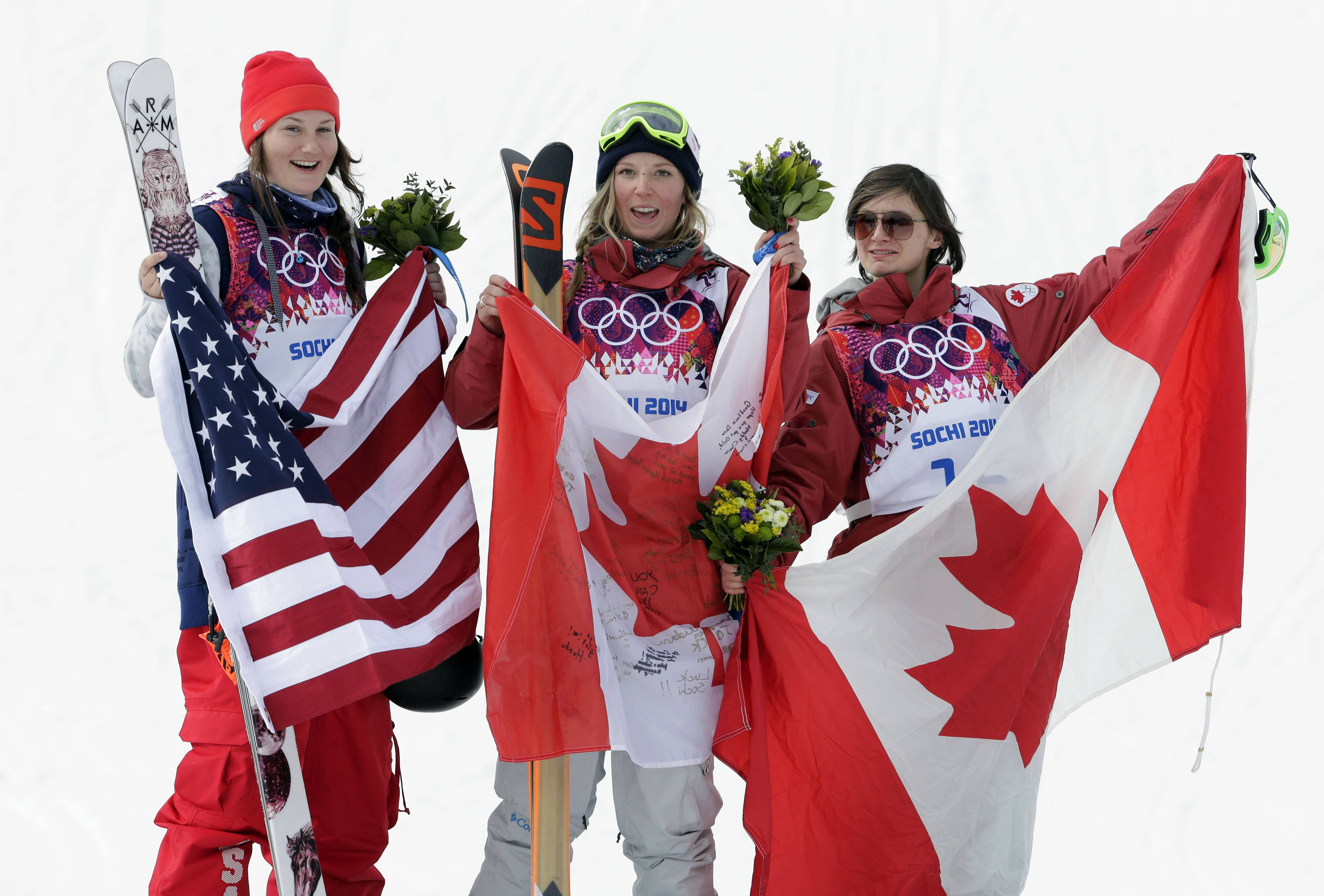 Canada's Dara Howell, center, celebrates on the podium with silver medalist Devin Logan of the United States, left, and Kim Lamarre, right,  also of Canada, after Howell took the gold medal in the women's freestyle skiing slopestyle final.