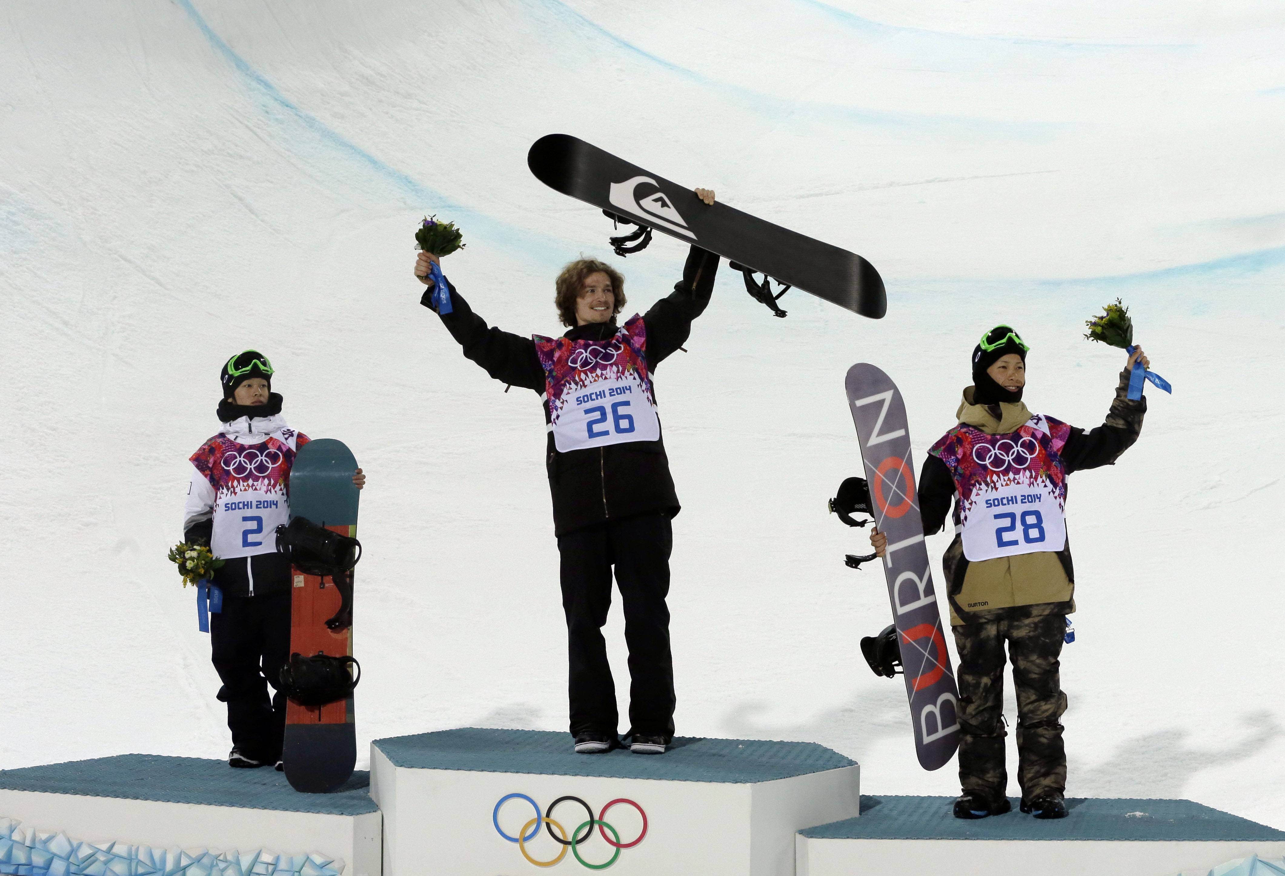 Switzerland's Iouri Podladtchikov celebrates on the podium with silver medalist  Ayumu Hirano of Japan, left, and bronze medalist Taku Hiraoka, also of Japan, after he won the gold medal in the men's snowboard halfpipe final.