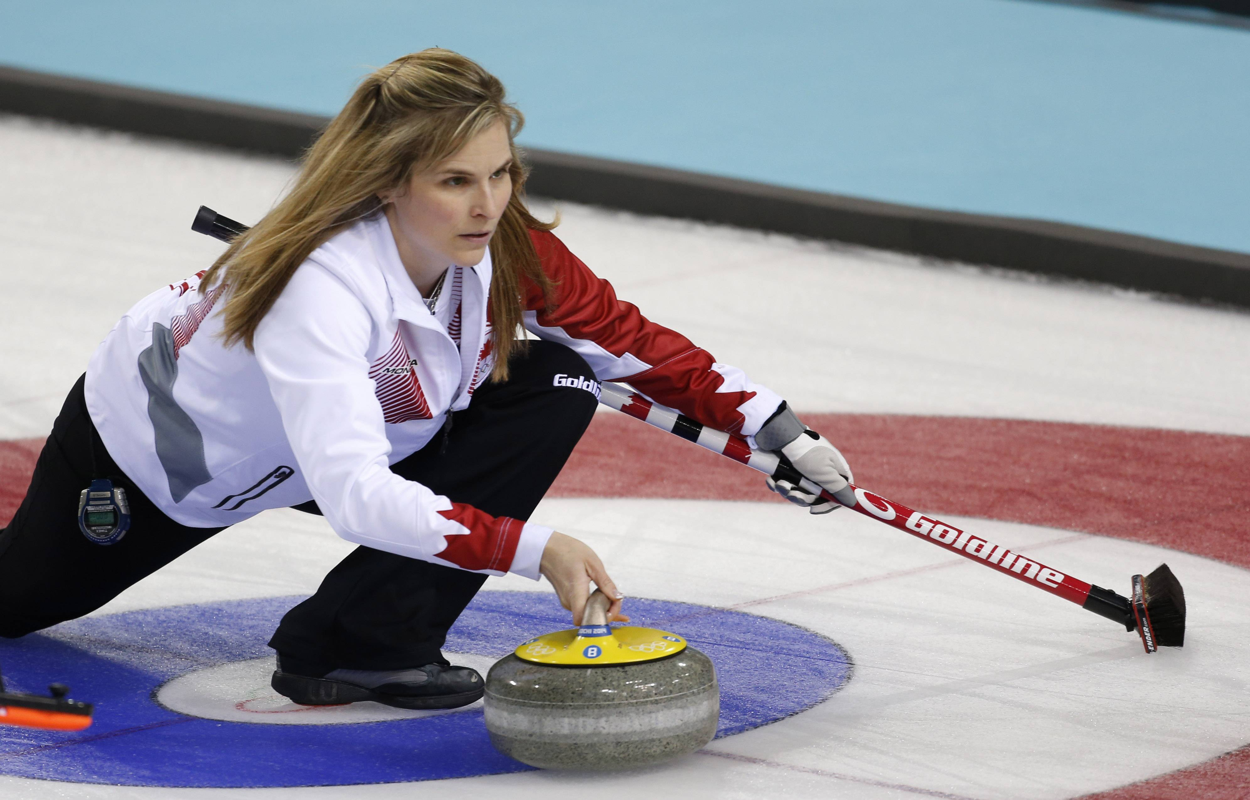 Canada's skip Jennifer Jones delivers the rock to her during women's curling competition against Sweden.