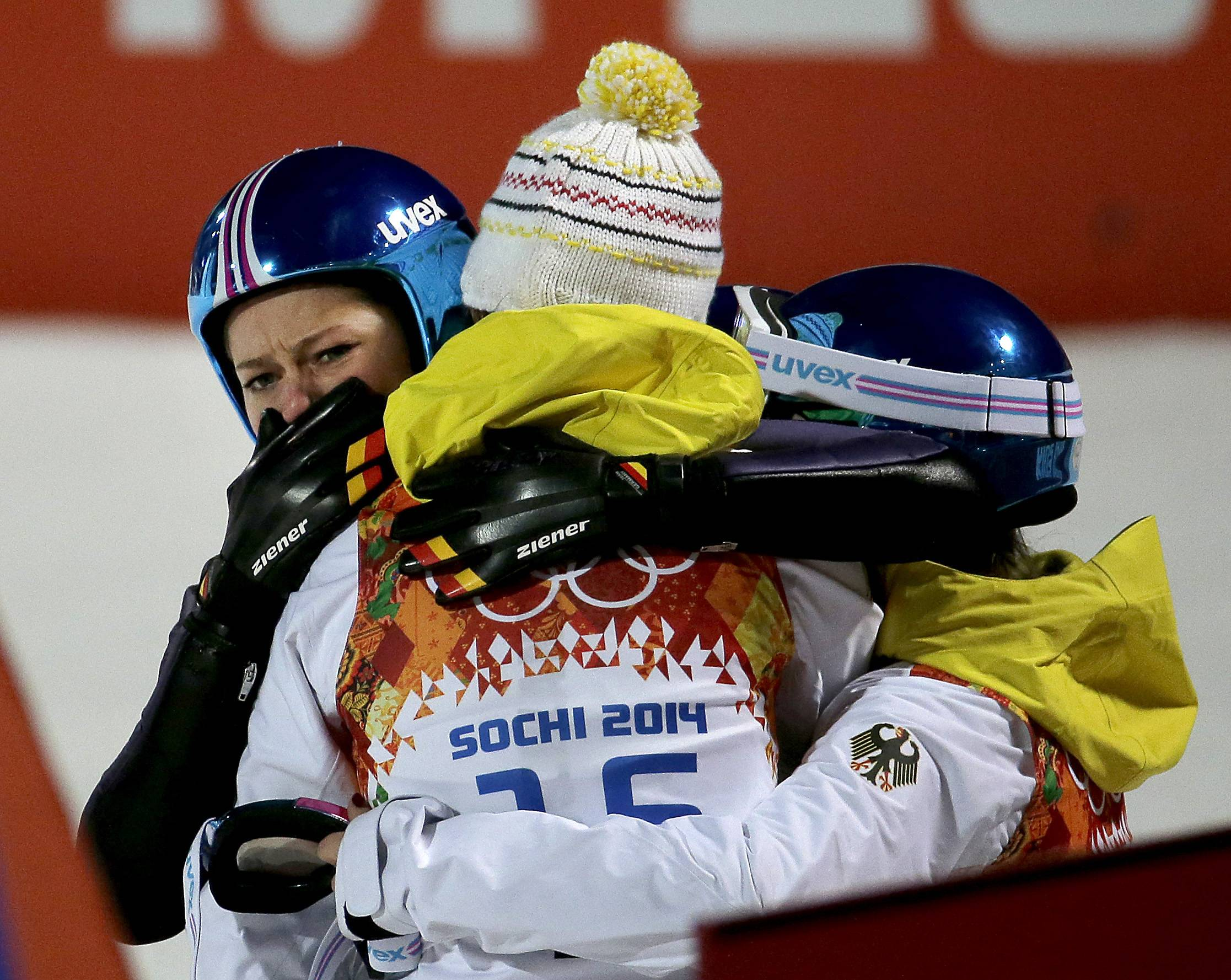 Germany's Carina Vogt, left, is hugged by teammates after winning the gold during the women's normal hill ski jumping final.