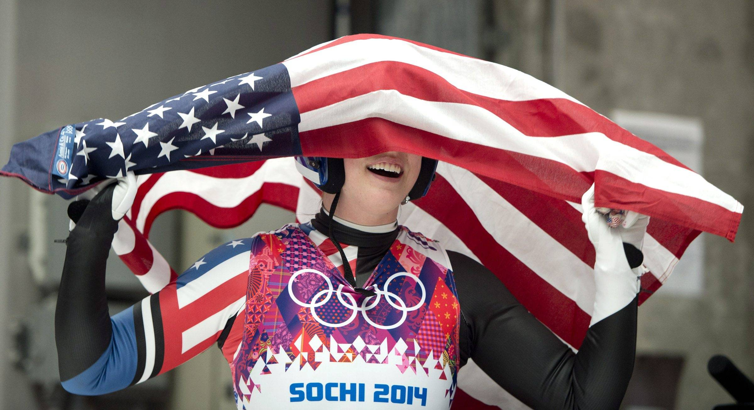 Erin Hamlin of the United States celebrates with the American flag after finishing her final run to win the bronze medal in the women's singles luge competition.
