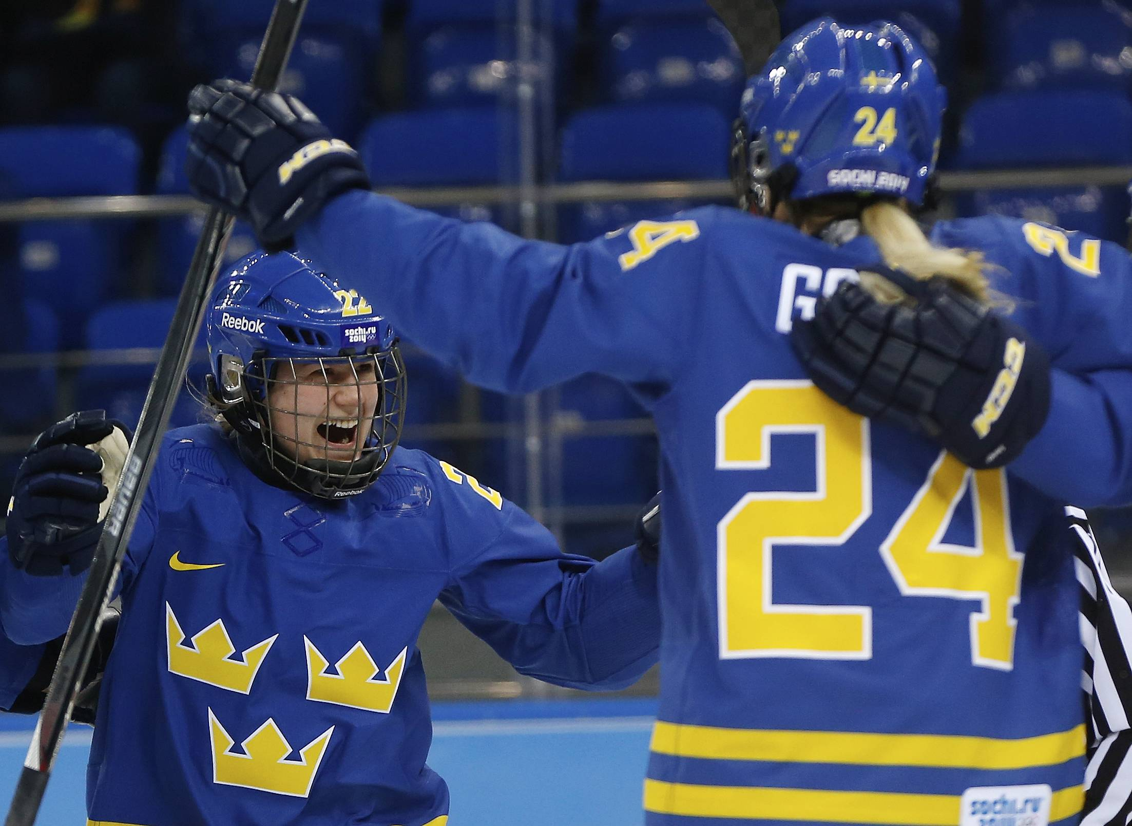 Emma Eliasson of Sweden, left, celebrates with teammates after Emma Nordin's goal against Germany during the first period of the 2014 Winter Olympics women's ice hockey game .