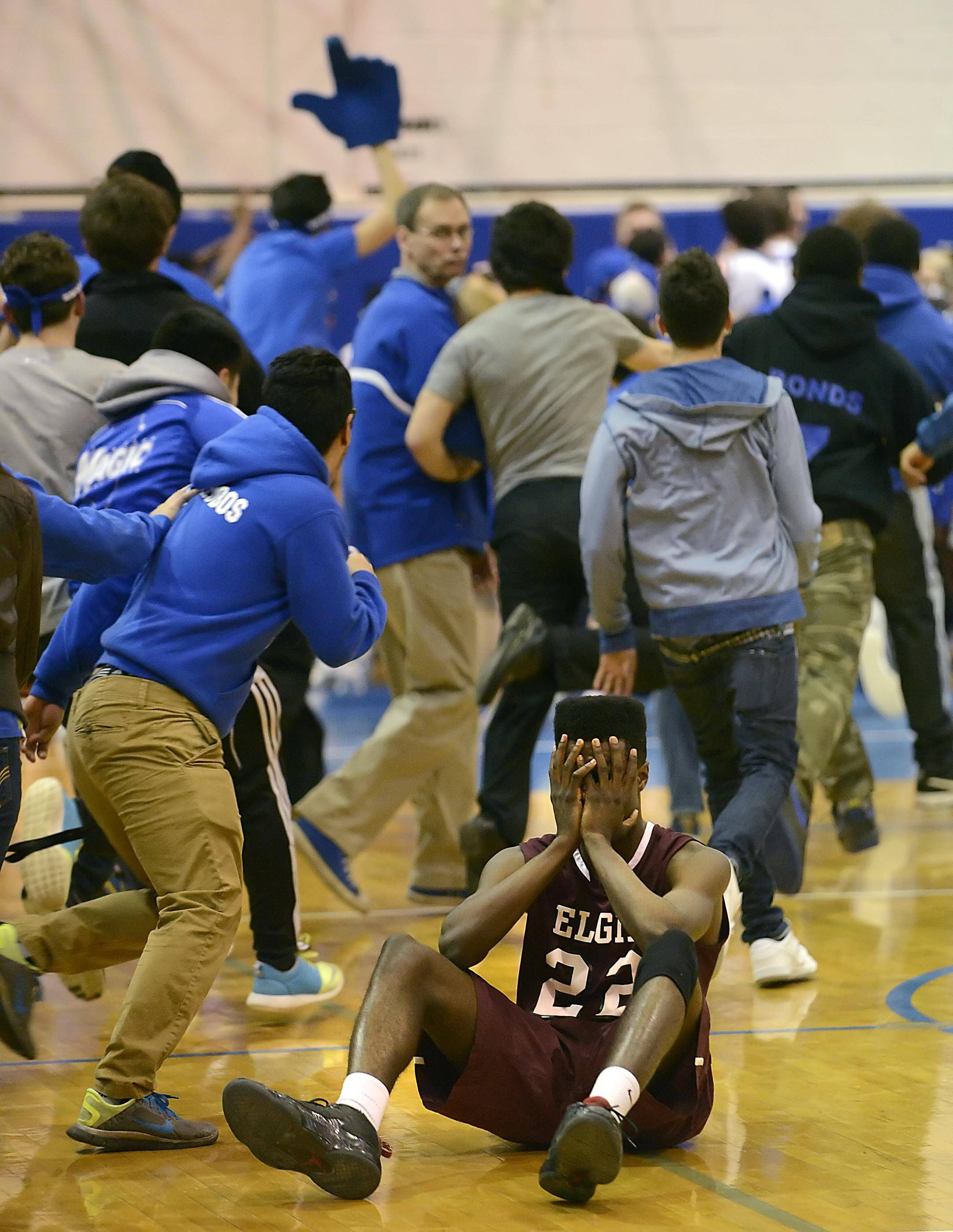 Elgin's Desmond Sanders reacts as Larkin students rush the floor after the Royals beat the Maroons in the final seconds of Friday's game in Elgin.