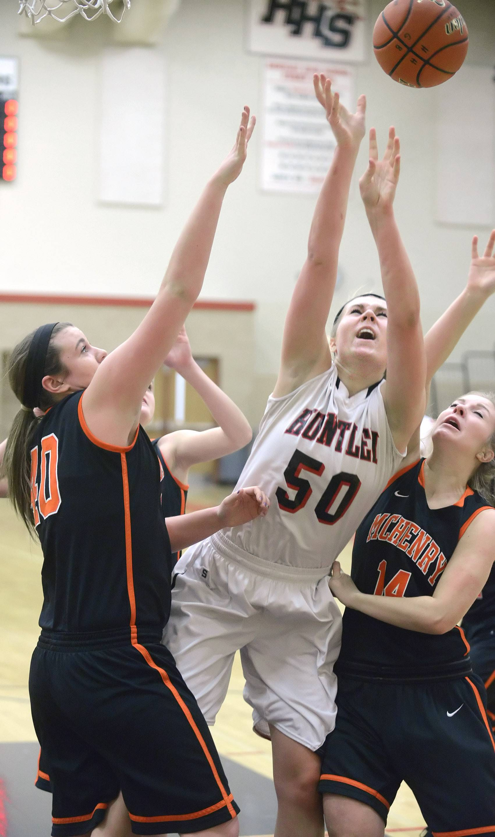 Huntley's Ali Andrews (50) is swarmed by McHenry's Mckayla Snedeker, left, and Greta Taylor during Wednesday's game.