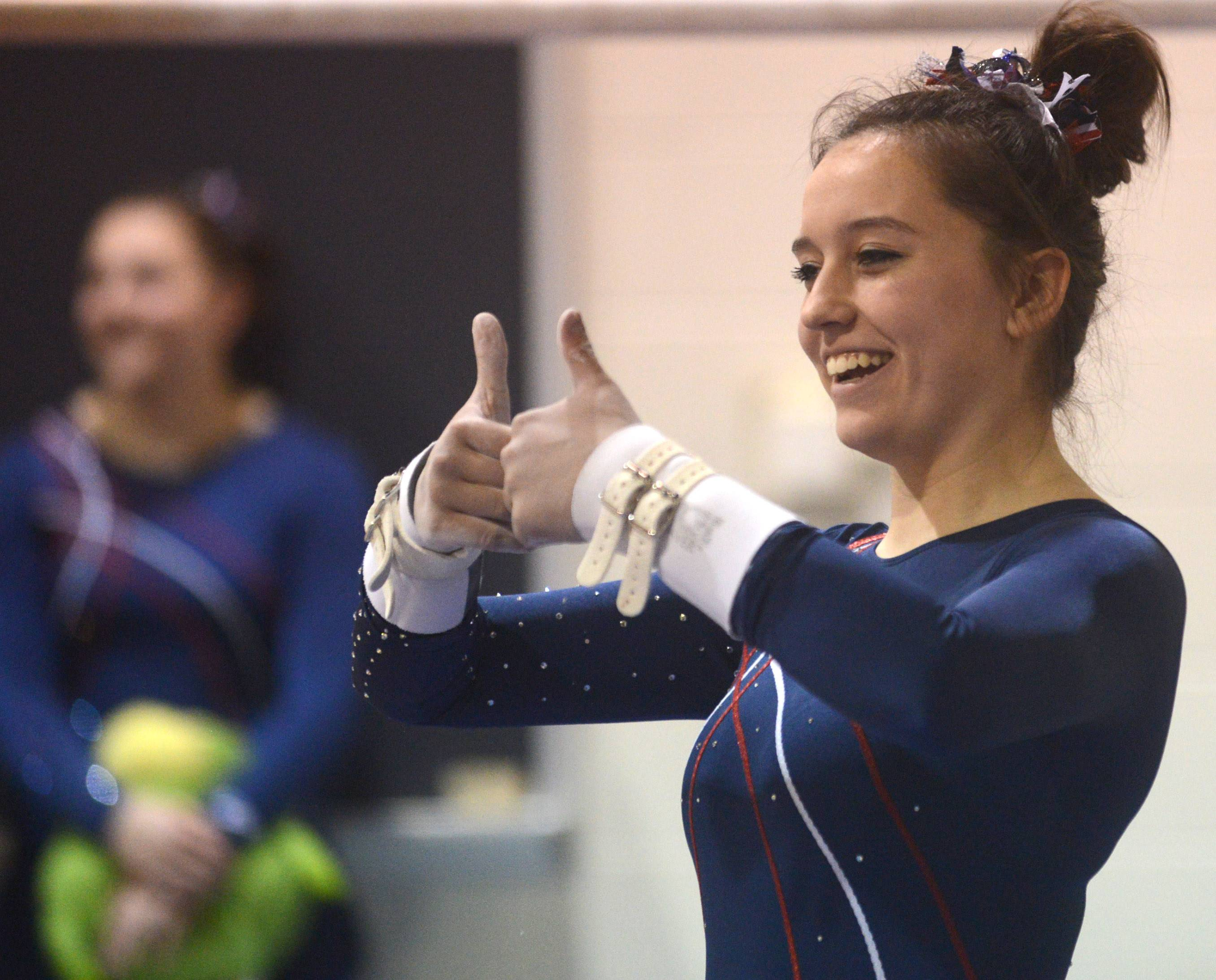 Conant's Ali Kelly acknowledges fans before her uneven parallel bars routine Monday in Barrington.