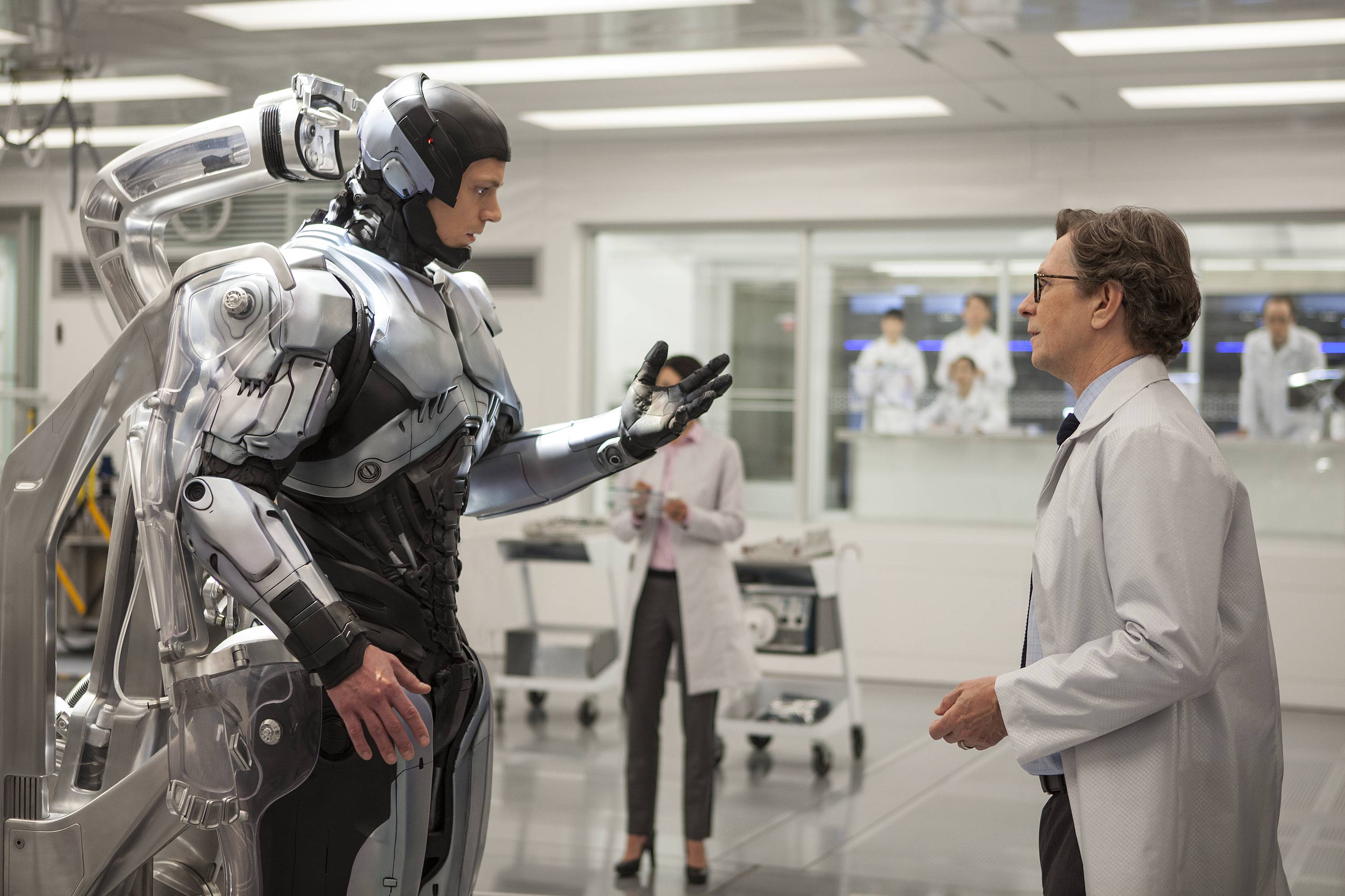 "Detroit detective Alex Murphy (Joel Kinnaman), left, tries out his new steel body with the help of scientist Dennett Norton in ""RoboCop."""