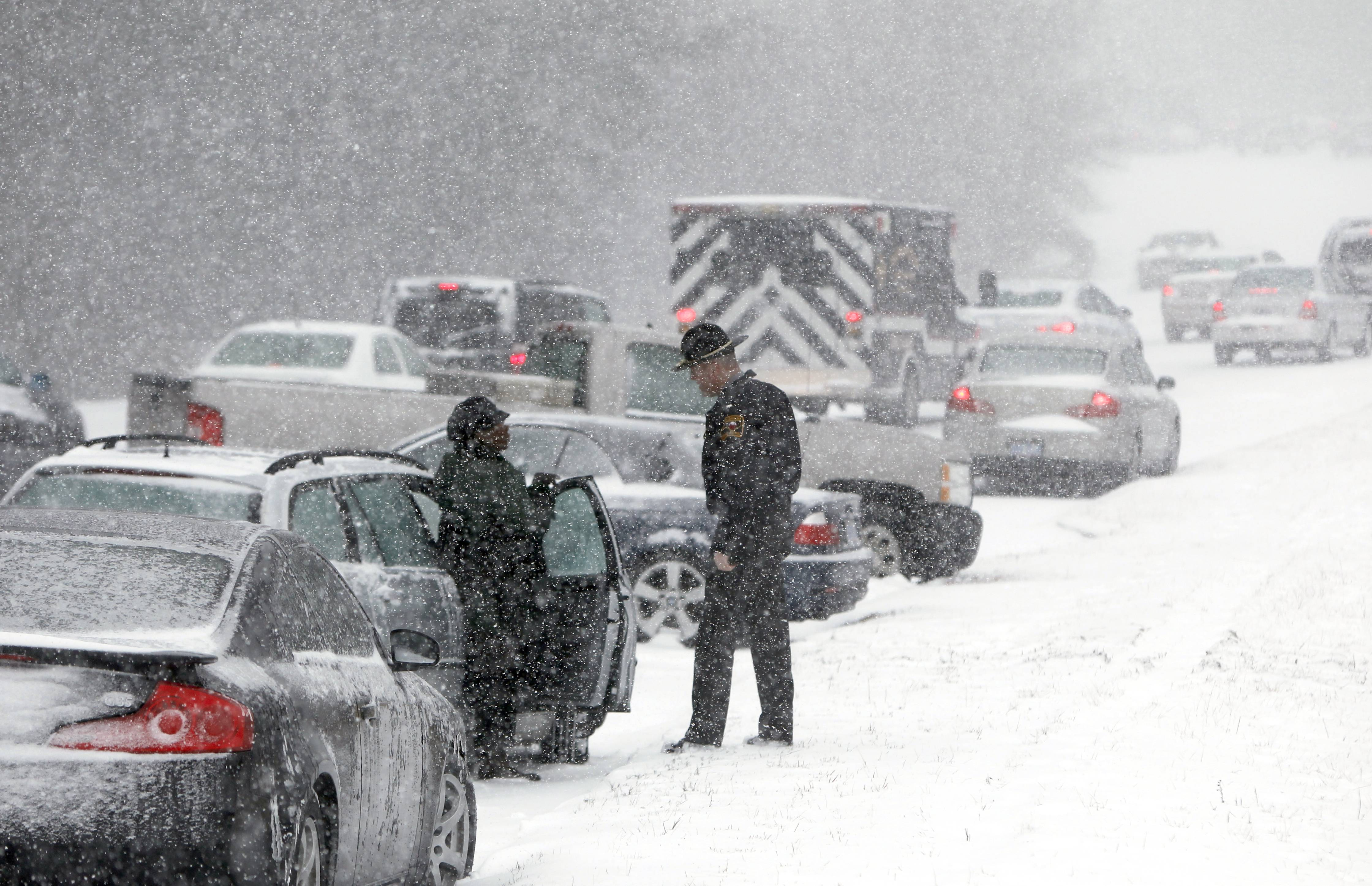 A Highway Patrol officer checks on a stranded motorist during a winter storm Wednesday in Durham, N.C.