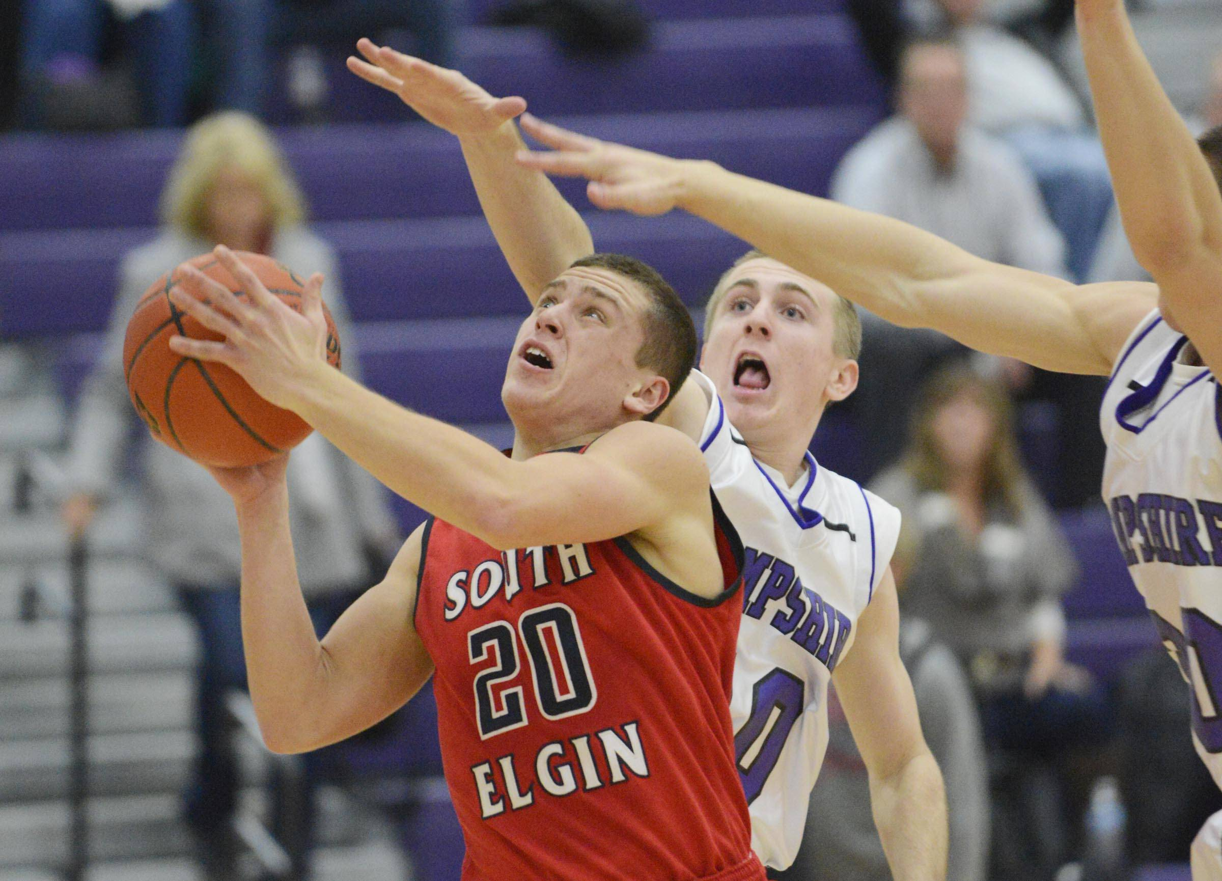 South Elgin's Matt McClure cuts through the defense of Hampshire's Drew Doran and Austin Spaeth.