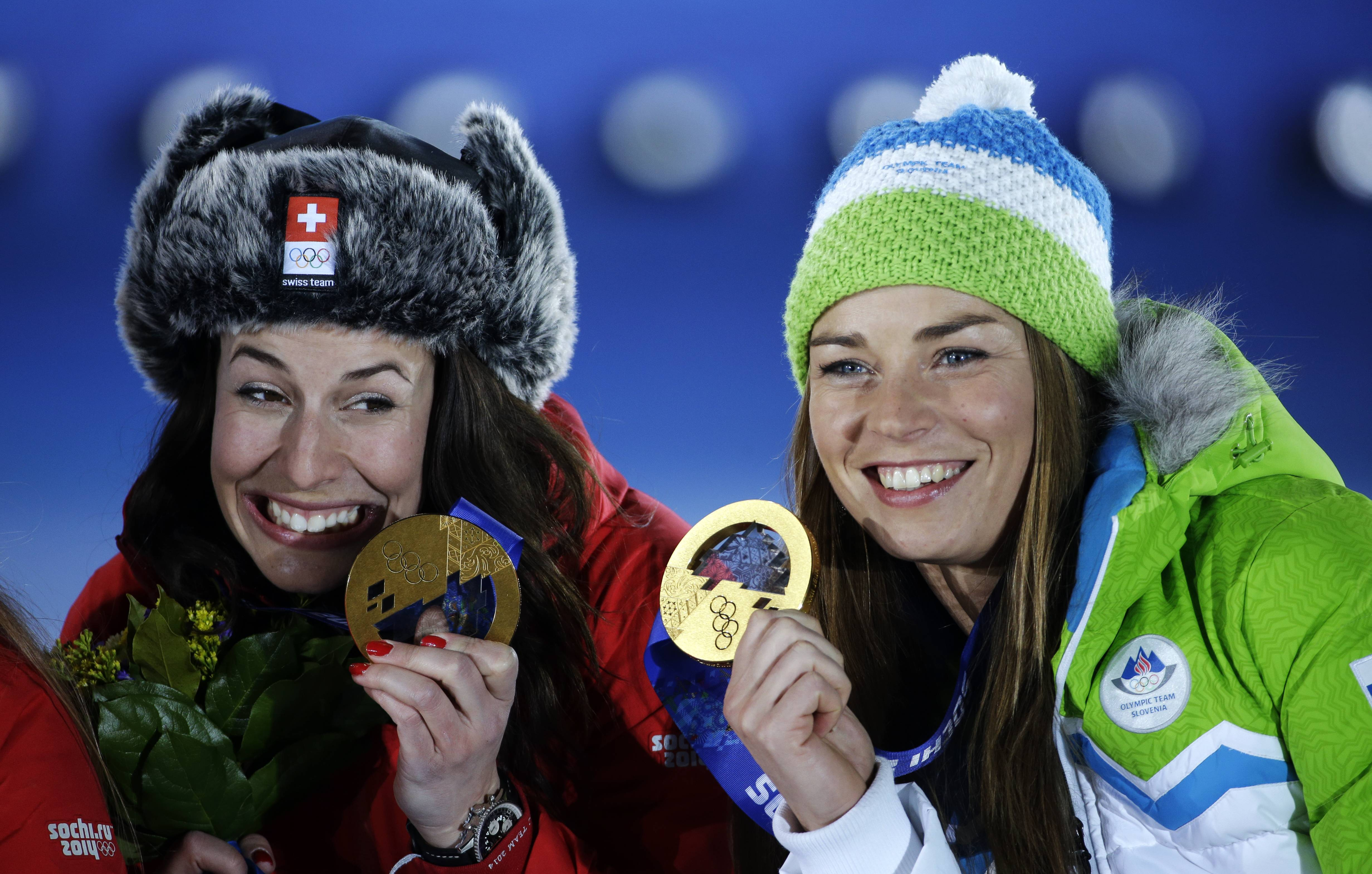 Dominique Gisin of Switzerland, left, and Tina Maze of Slovenia, right, who tied for the gold medal in the women's downhill pose during their medals ceremony.