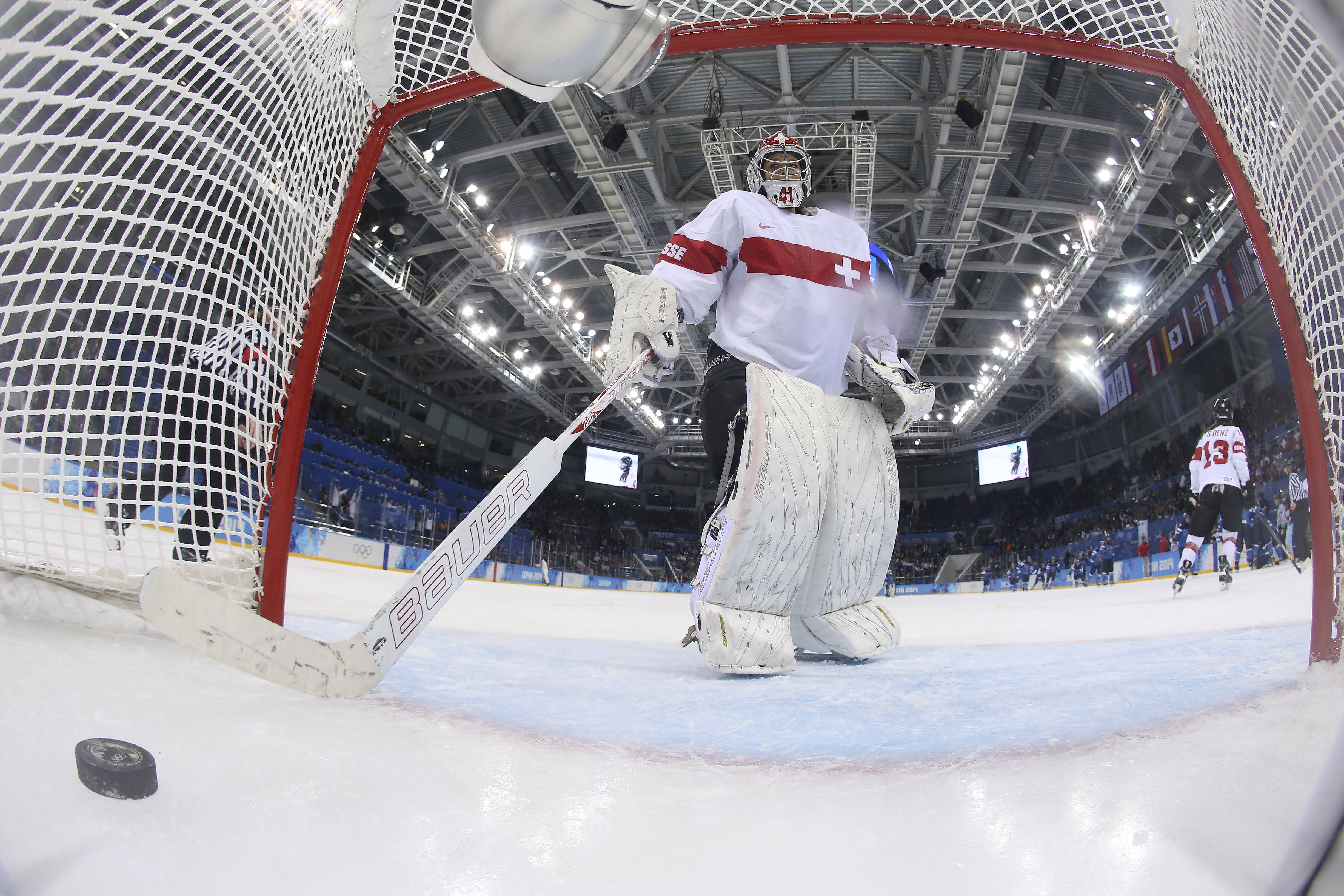 Goalkeeper Florence Schelling of Switzerland scoops the puck out of the net Wednesday after Jenni Hiirikoski of Finland scored in overtime to give Finland a 4-3 victory at the 2014 Winter Olympics in Sochi, Russia.