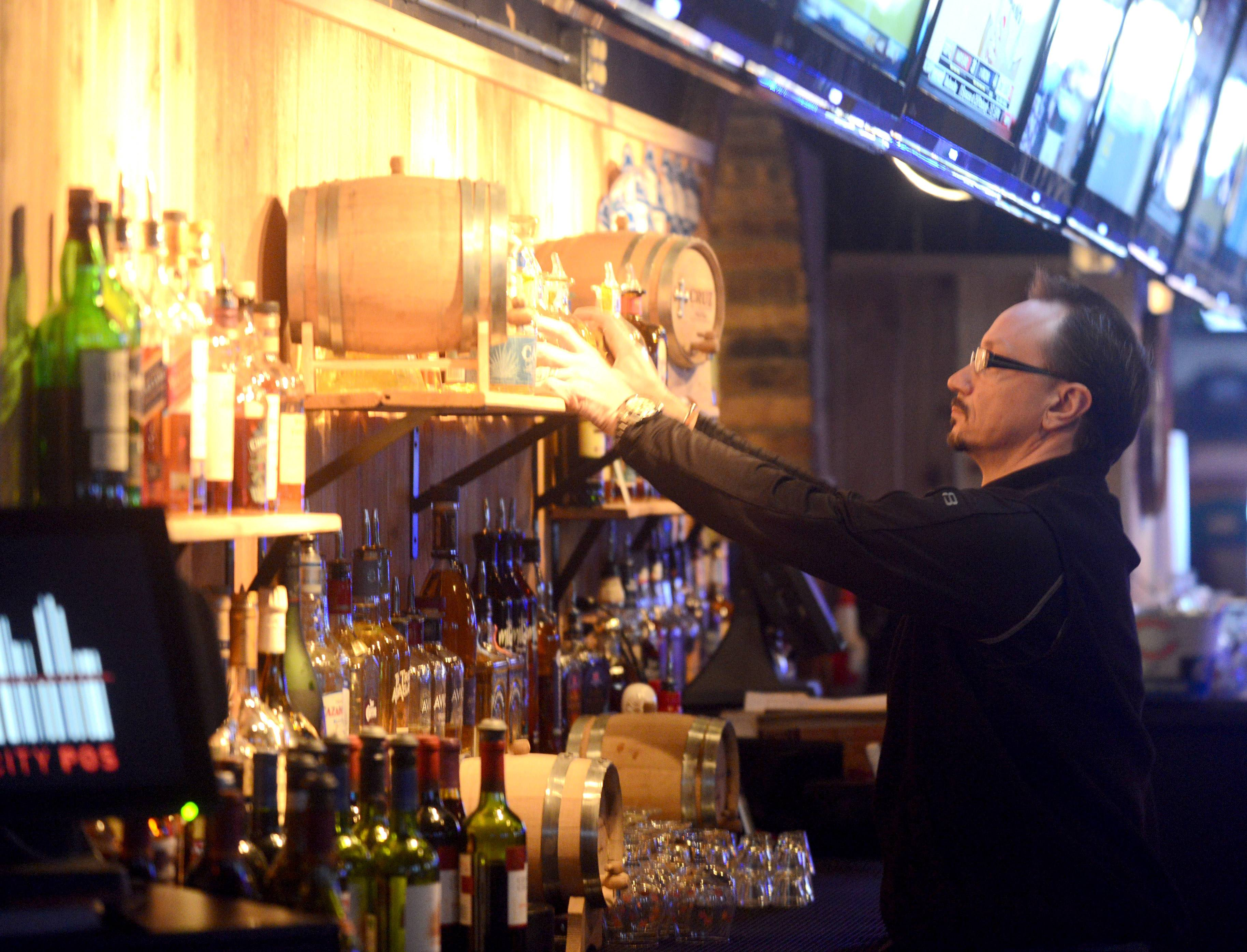 Co-owner Chad Severson arranges bottles behind the bar at M T Barrels in Schaumburg.