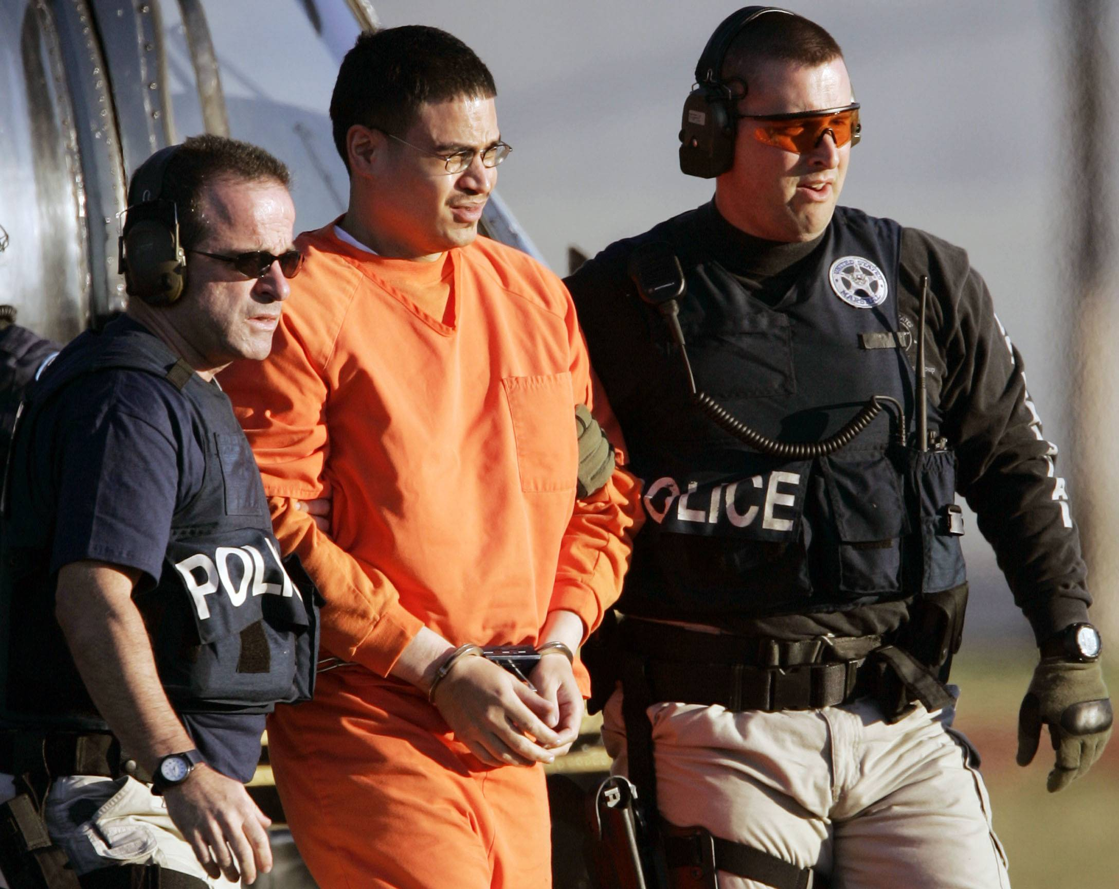 In this Jan. 5, 2006, file photo, Jose Padilla, center, is escorted by federal marshals on his arrival in Miami. Miami U.S. District Judge Marcia Cooke scheduled a Wednesday afternoon Feb. 12 hearing for Padilla. He originally was sentenced to 17 years of prison for terrorism support and conspiracy convictions. A federal appeals court ruled in 2011 that the sentence was too lenient, given Padilla's lengthy criminal record and terrorist training at an al-Qaida camp in Afghanistan.