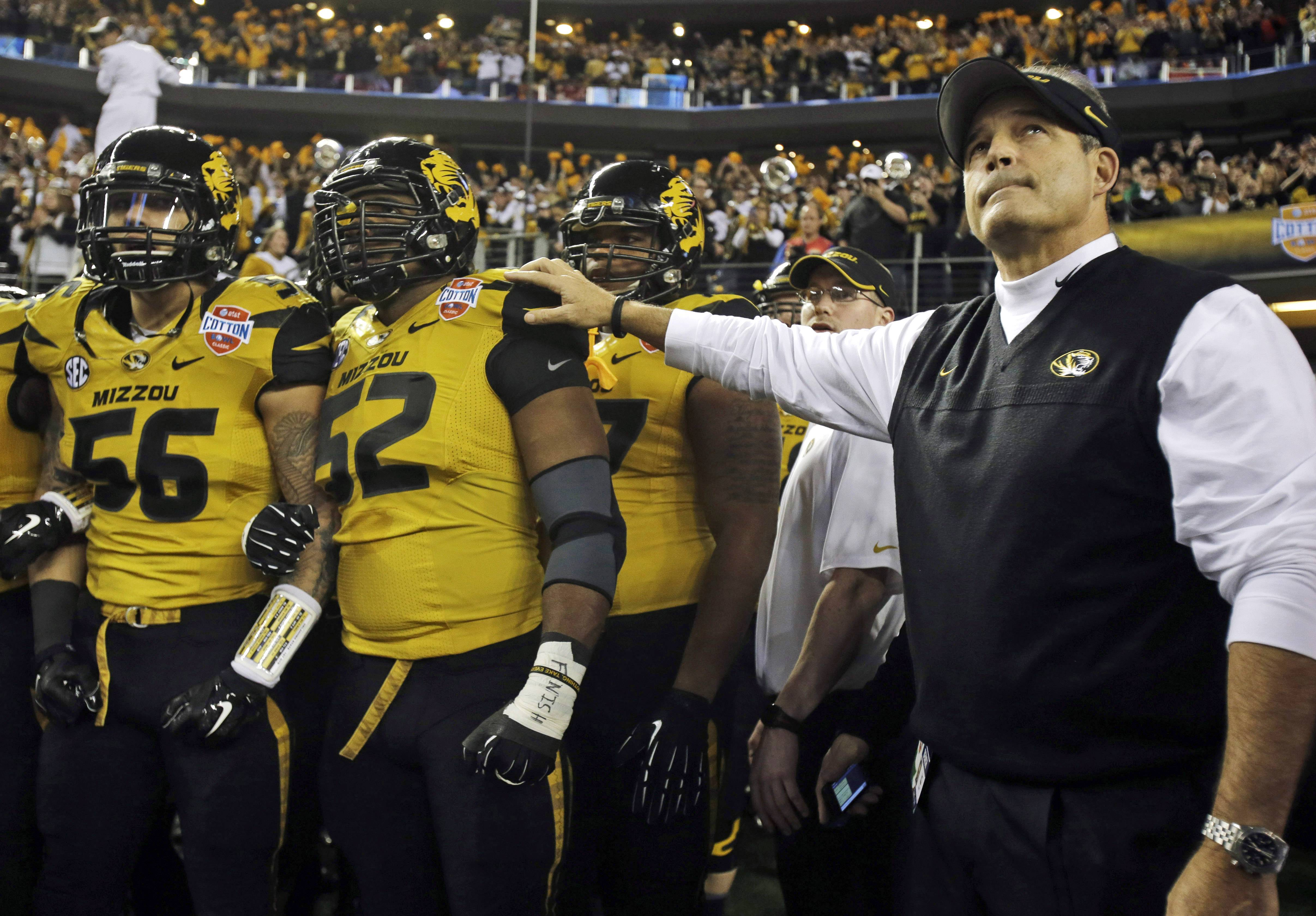 Missouri head coach Gary Pinkel, right, and players, including offensive linesman Robert Luce (56) and defensive lineman Michael Sam (52), prepare to take the field for the Cotton Bowl NCAA college football game against Oklahoma State on Jan. 3. Sam, Missouri's All-America defensive end came out to the entire country Sunday and could become the first openly gay player in America's most popular sport.