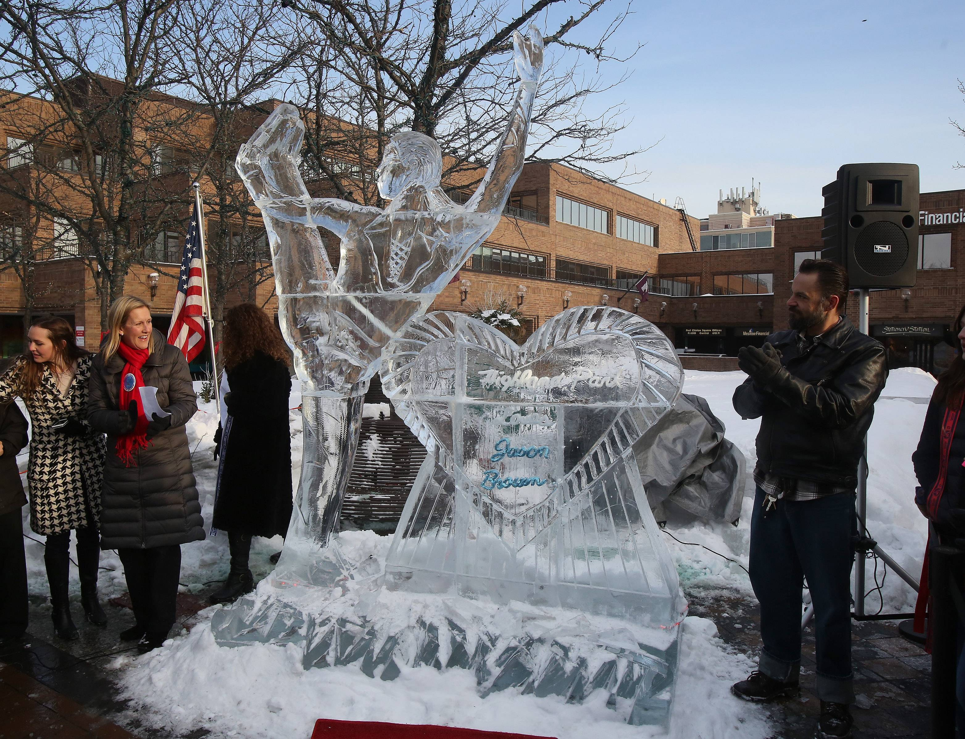 Highland Park Mayor Nancy Rotering, left, and ice sculptor Kristopher Duschen unveil the 10-foot ice sculpture of Olympic figure skater Jason Brown in the city's Port Clinton Square on Wednesday. Brown has won a bronze medal and is hoping for more this weekend when he skates in the individual events.