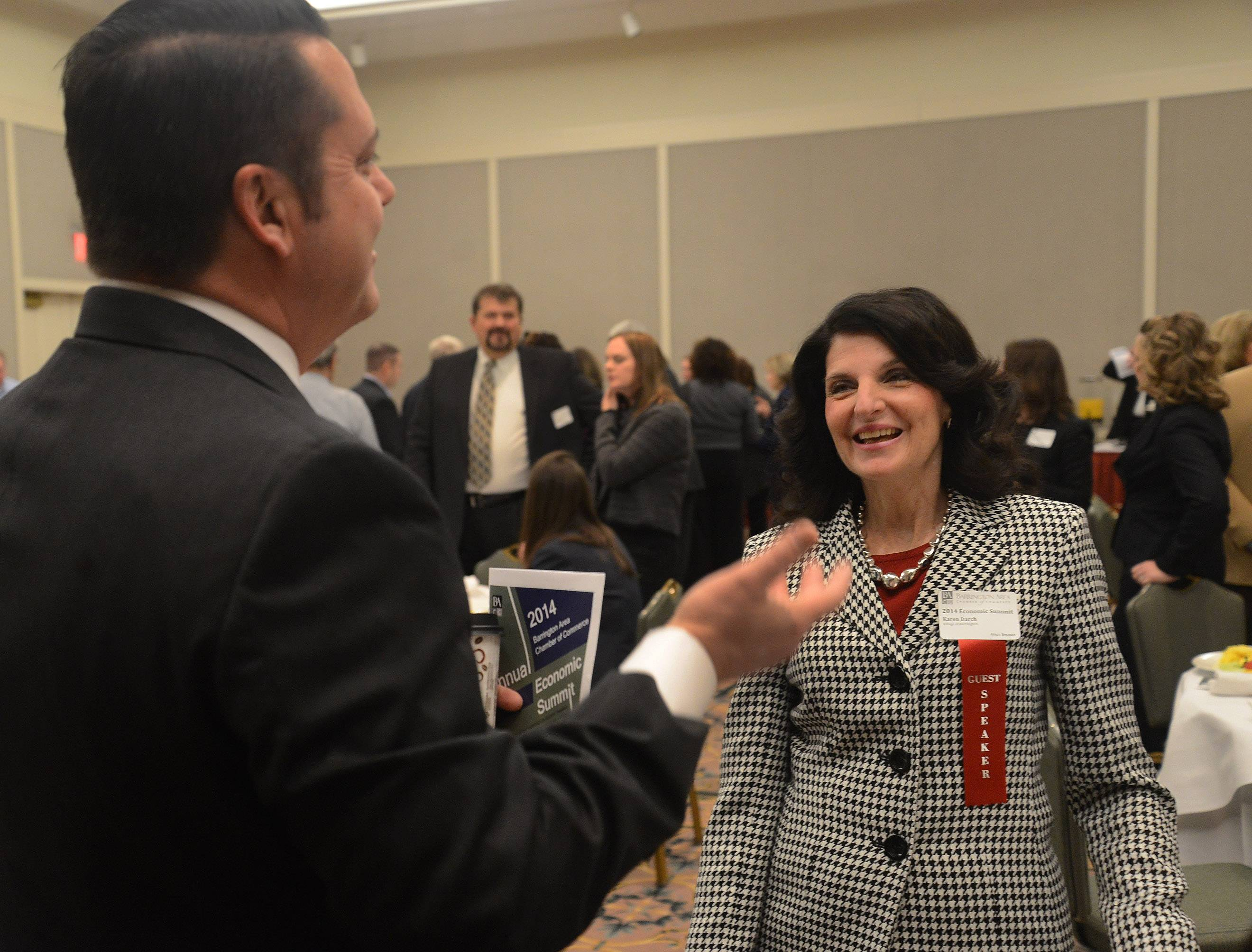 Jon Stickney, president of Barrington Bank, talks with Barrington Village President Karen Darch at the 2014 annual Economic Summit hosted Wednesday by the Barrington Area Chamber of Commerce.