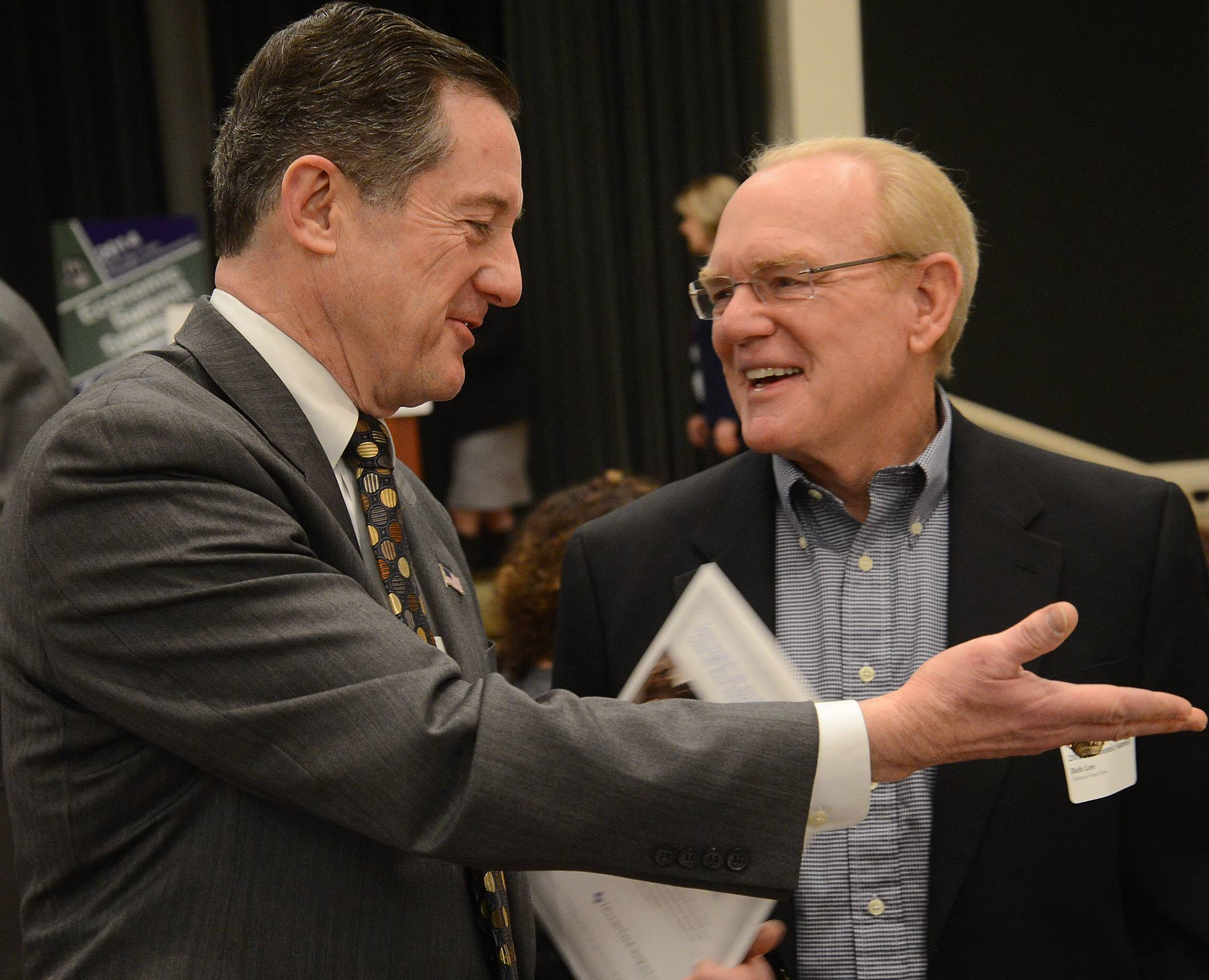 Joseph Connelly of BMO Harris Bank, left, talks with Bob Lee, of Enhance Your View, before the 2014 annual Economic Summit hosted Wednesday by the Barrington Area Chamber of Commerce.