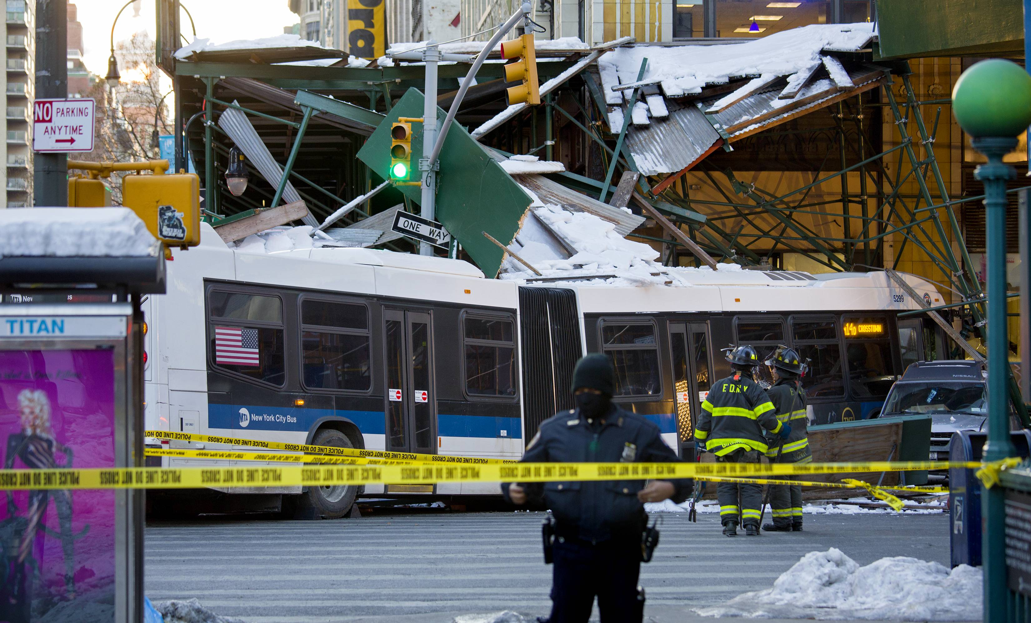 A Metropolitan Transportation Authority bus rests against scaffolding at 14th Street and 7th Avenue in New York, Wednesday, Feb. 12, 2014, after an early morning collision between the bus and a truck. One person was killed and at least four were injured in the crash, that also involved several parked vehicles.