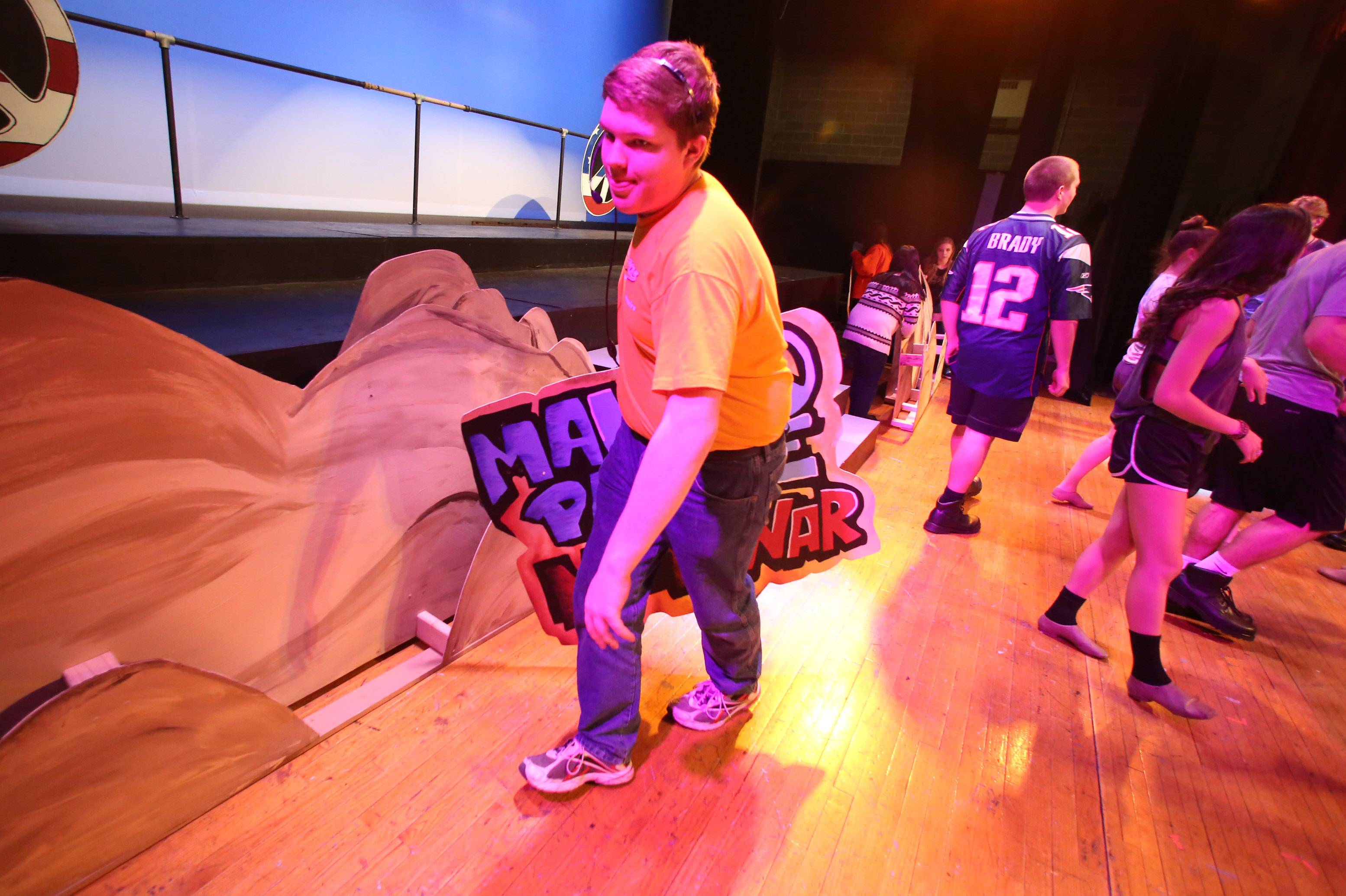 Floor manager Ed Chmiel, a junior, takes a sign offstage during a rehearsal for Carmel Catholic High School's Street Scenes.