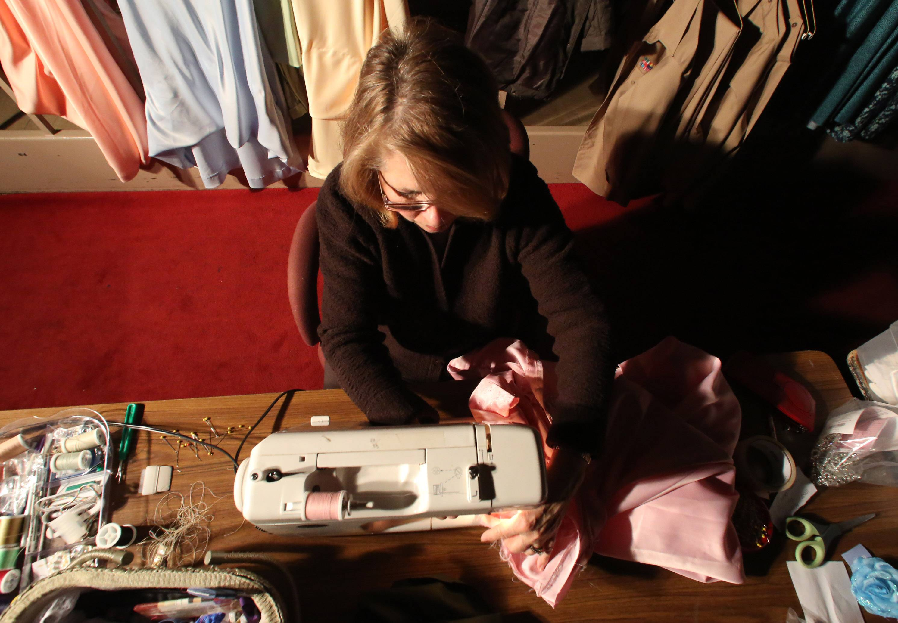 Lillian Jarrett of Gurnee sews costumes backstage during a rehearsal for Carmel Catholic High School's Street Scenes.