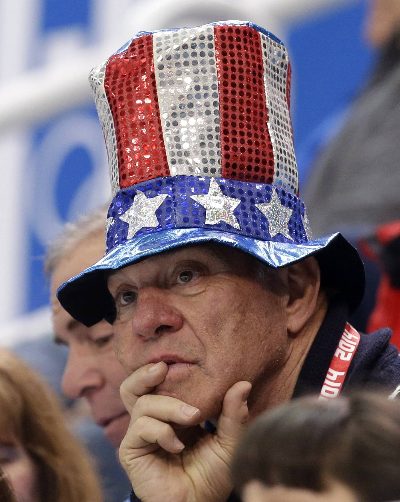 A spectator wearing a hat in the colours of the U.S. flag watches the pairs free skate figure skating competition.