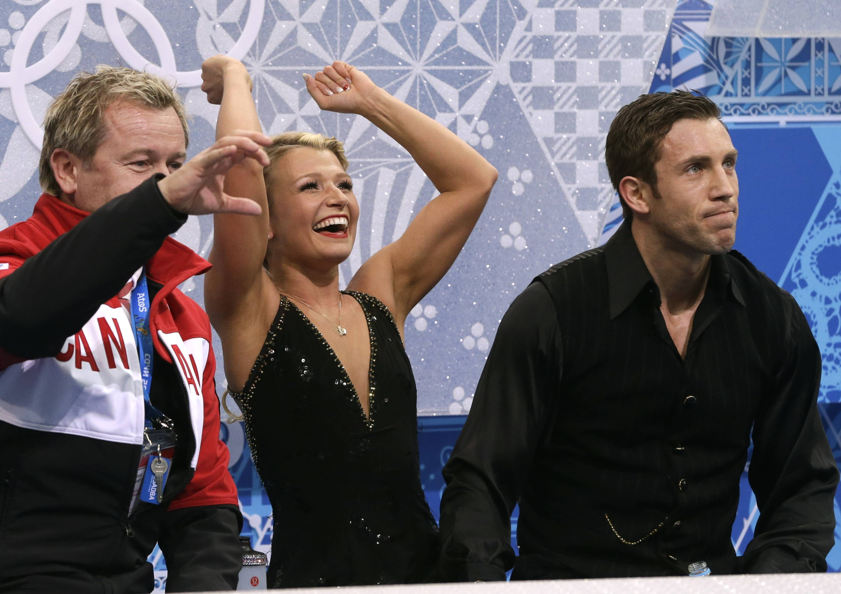 Kirsten Moore-Towers, center, gestures as she and Dylan Moscovitch of Canada wait in the results area after competing in the pairs free skate figure skating.