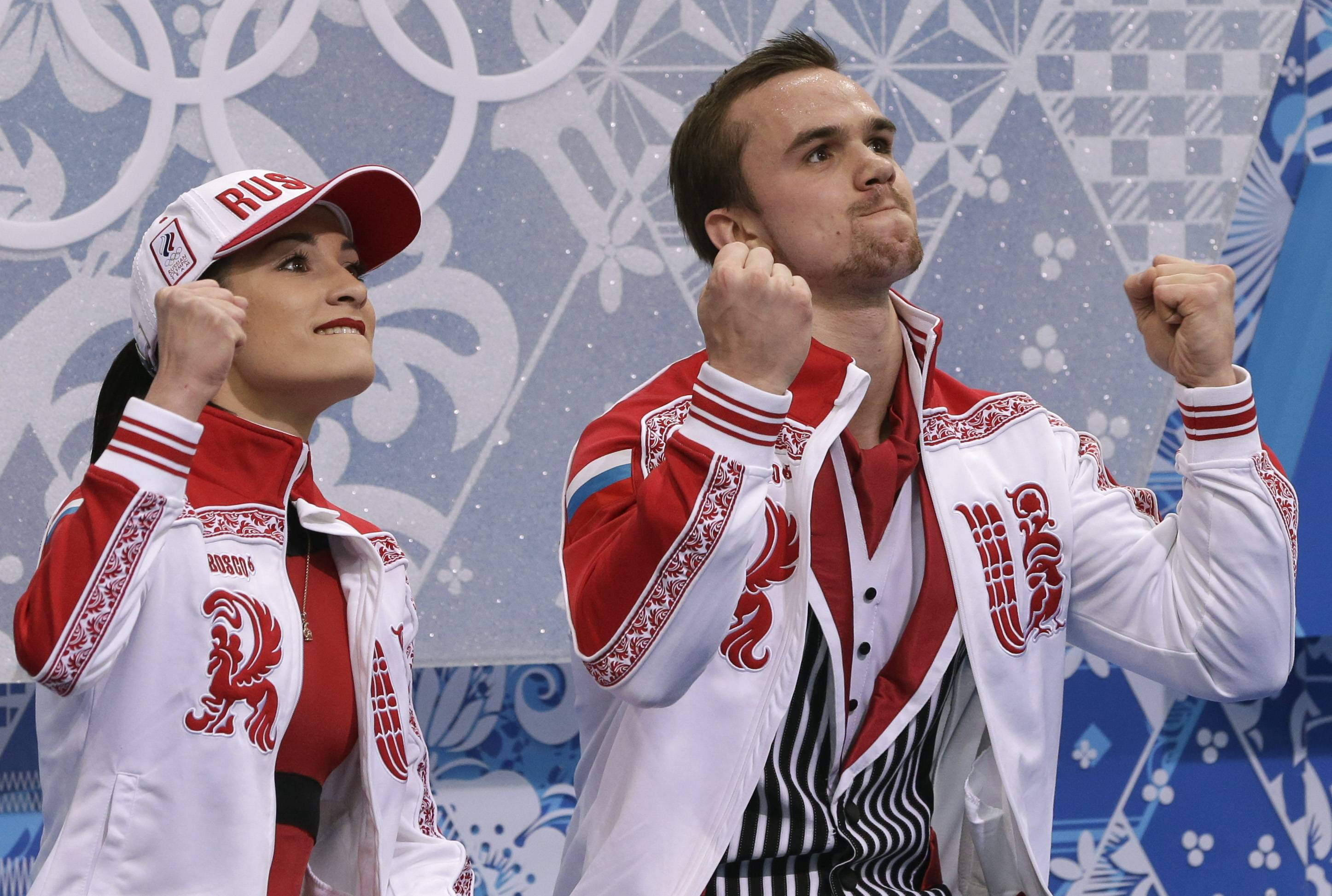 Ksenia Stolbova and Fedor Klimov of Russia react as they wait in the results area after competing in the pairs free skate figure skating.