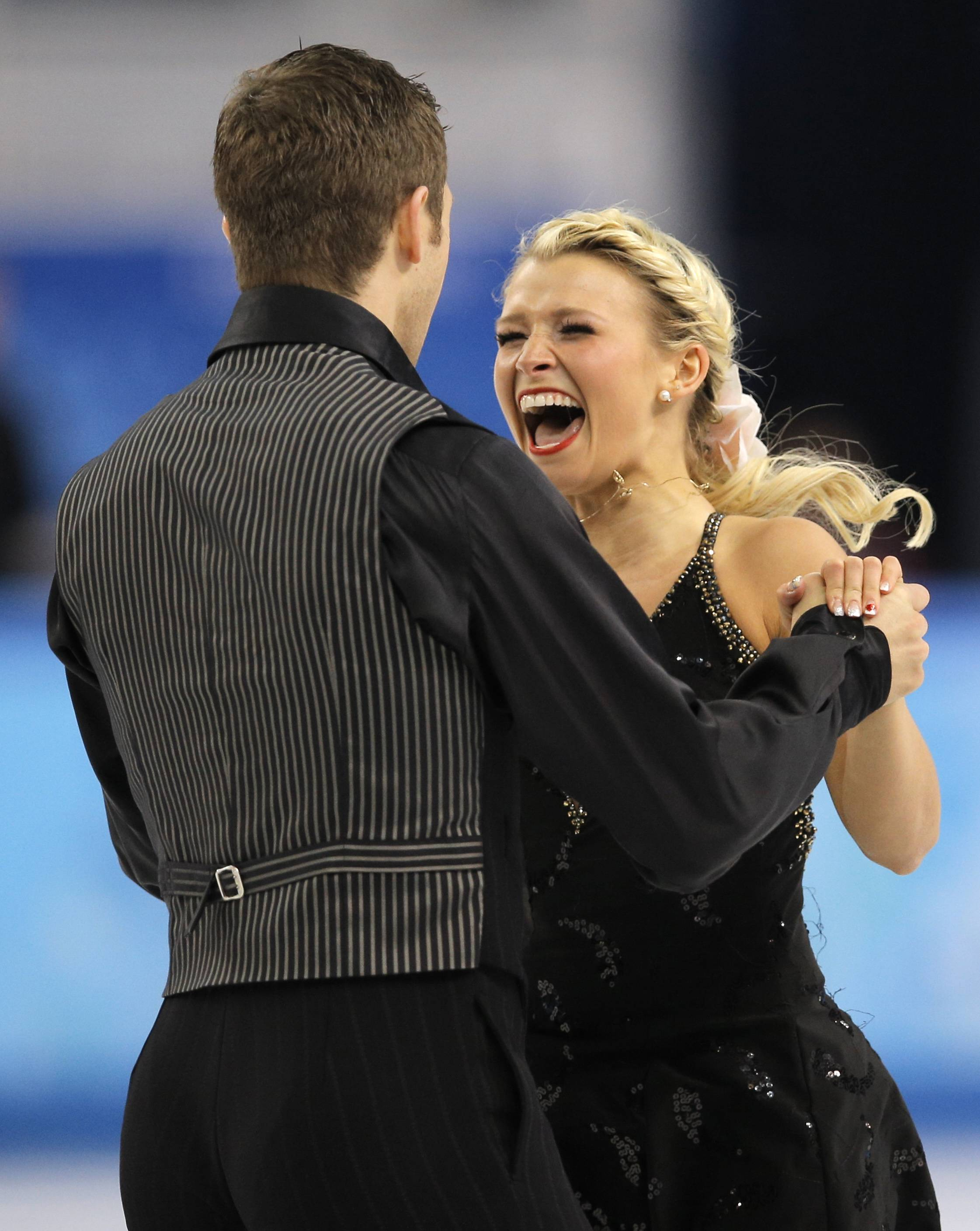 Kirsten Moore-Towers and Dylan Moscovitch of Canada react as they leave the ice after finishing their routine in the pairs free skate figure skating.