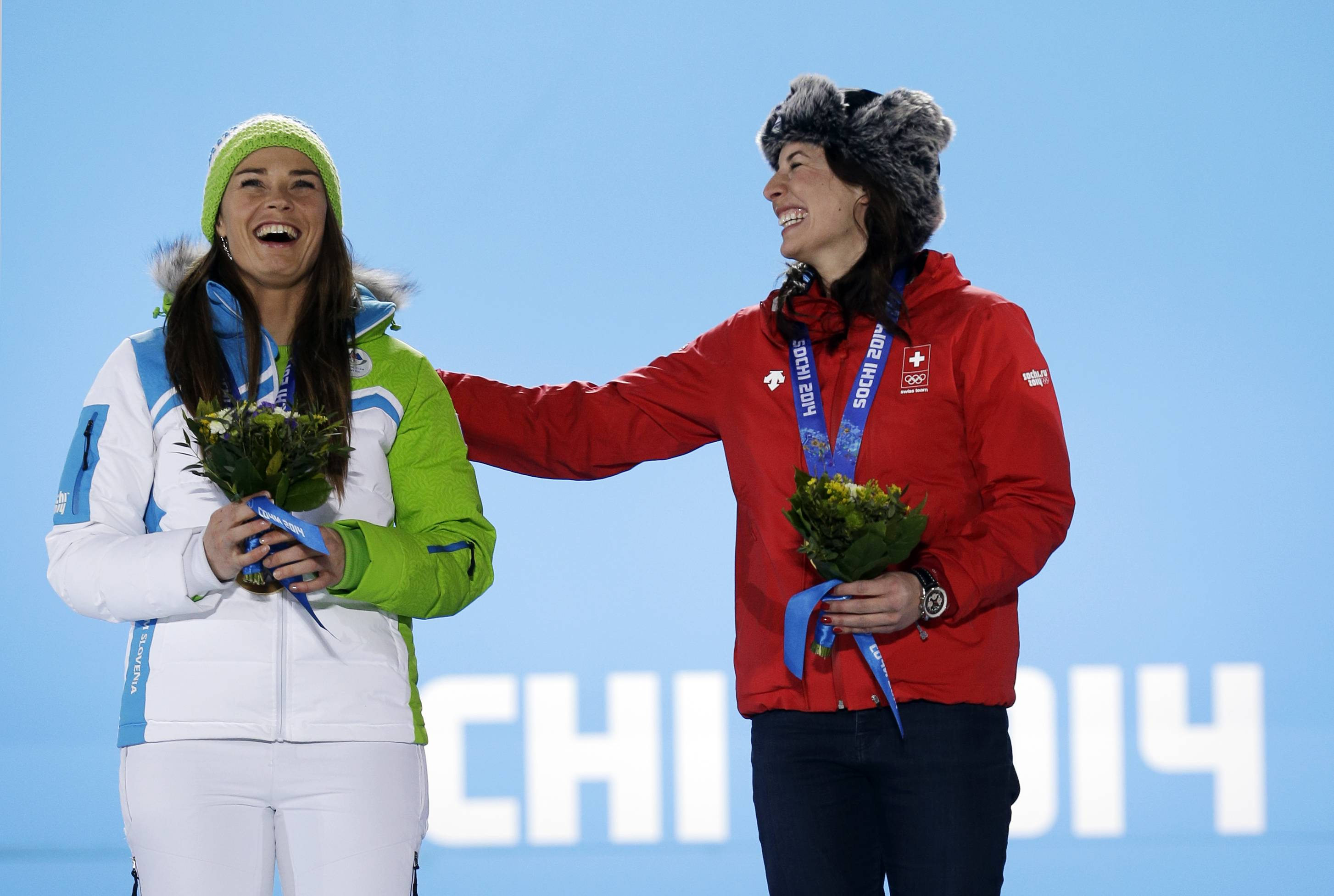 Dominique Gisin of Switzerland, right, smiles with Tina Maze of Slovenia, who tied for the gold medal in the women's downhill during their medals ceremony.