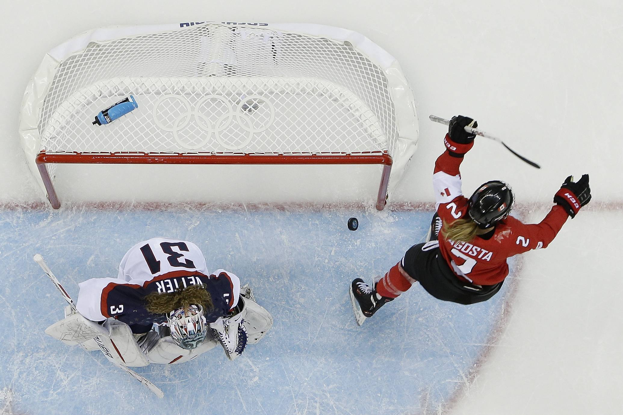 Meghan Agosta-Marciano of Canada celebrates her goal as USA Goalkeeper Jessie Vetter looks down at the ice in the third period of the 2014 Winter Olympics women's ice hockey game at Shayba Arena, Wednesday, Feb. 12, 2014, in Sochi, Russia. Canada defeated the United States 3-2.
