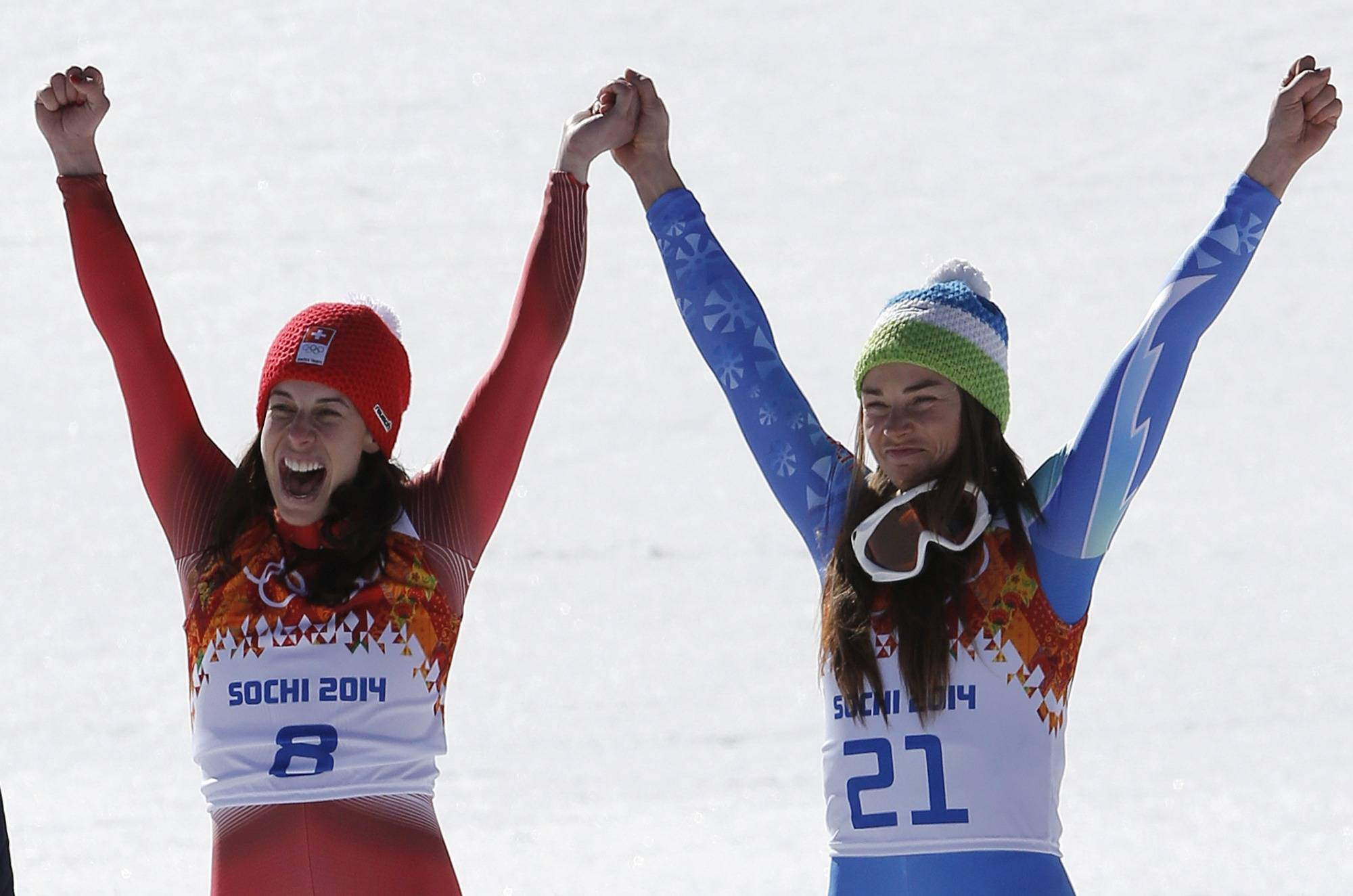 Women's downhill gold medalists Switzerland's Dominique Gisin, left, and Slovenia's Tina Maze, right, hold hands during a flower ceremony at the Sochi 2014 Winter Olympics, Wednesday, Feb. 12, 2014, in Krasnaya Polyana, Russia.