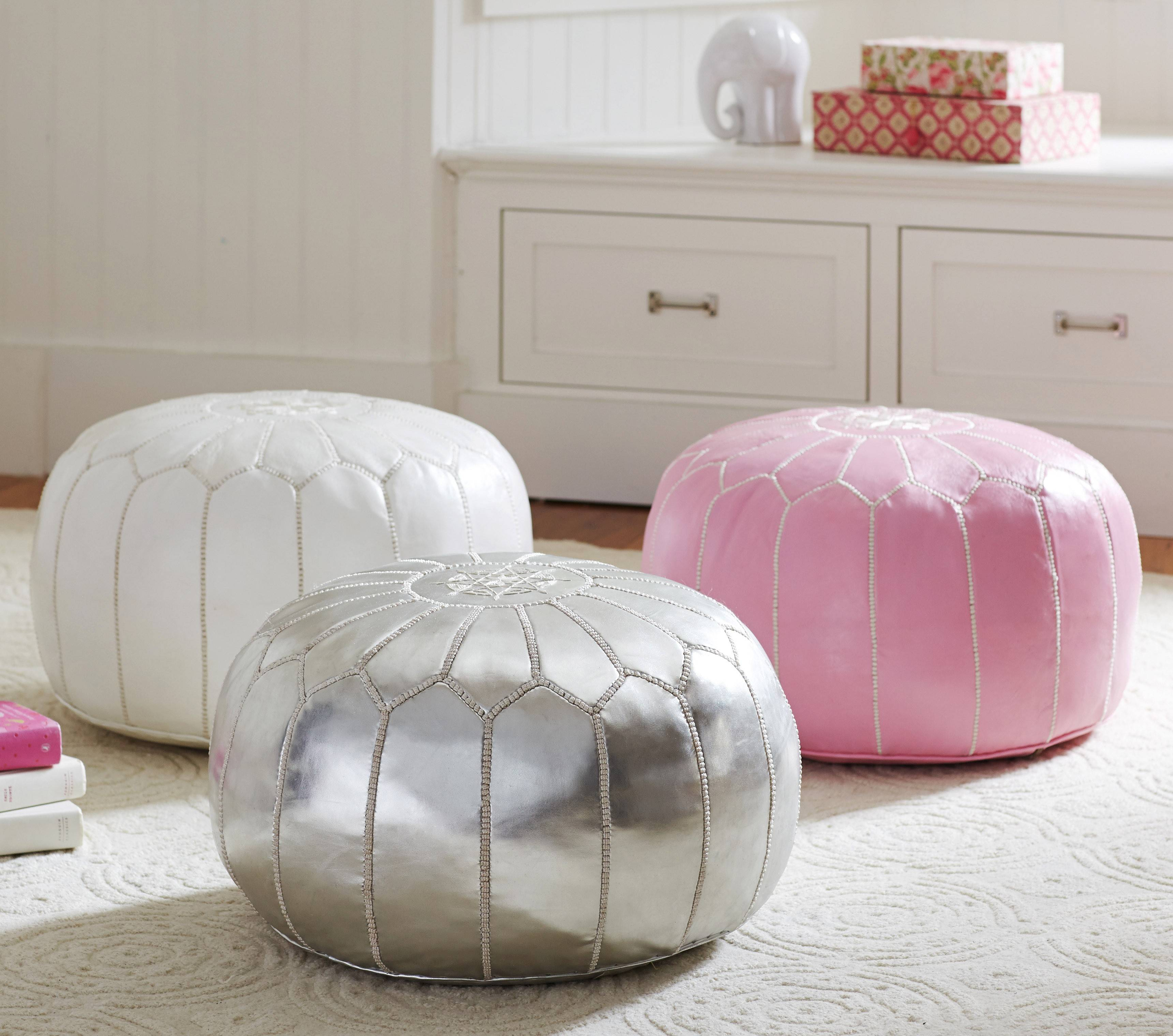 Adding in a few pink accessories freshens a great room or living room for spring. A pink pouf is a practical piece with flair.