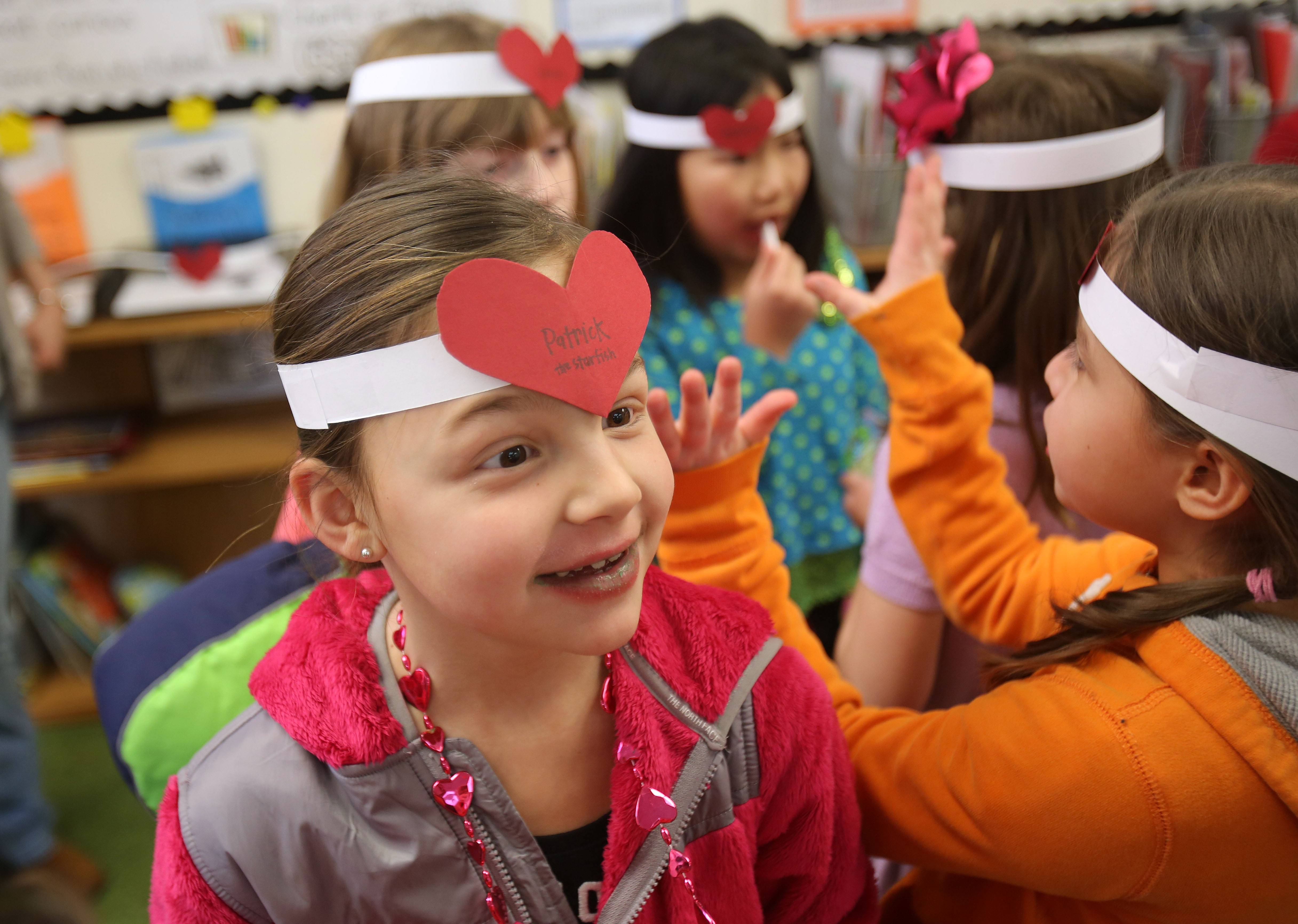 Third-grader Anna DeRosa and classmates at Butterfield Elementary School in Libertyville play a version of the game Headbandz. They put hearts on their foreheads and tried to guess who they are during a Valentine's Day party Thursday.