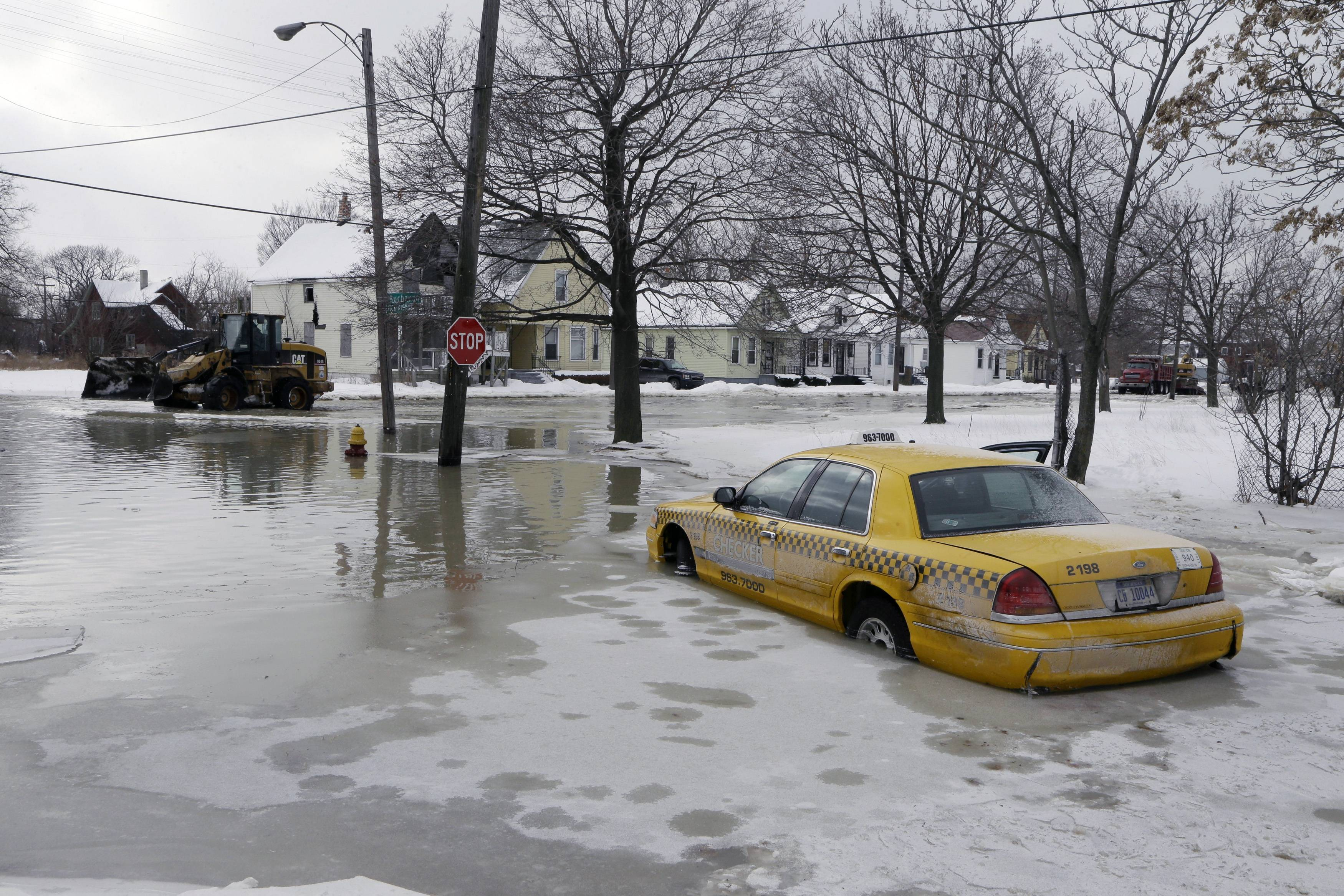 A taxi cab is surrounded by water on a flooded street after a water main break flooded several blocks in Detroit.