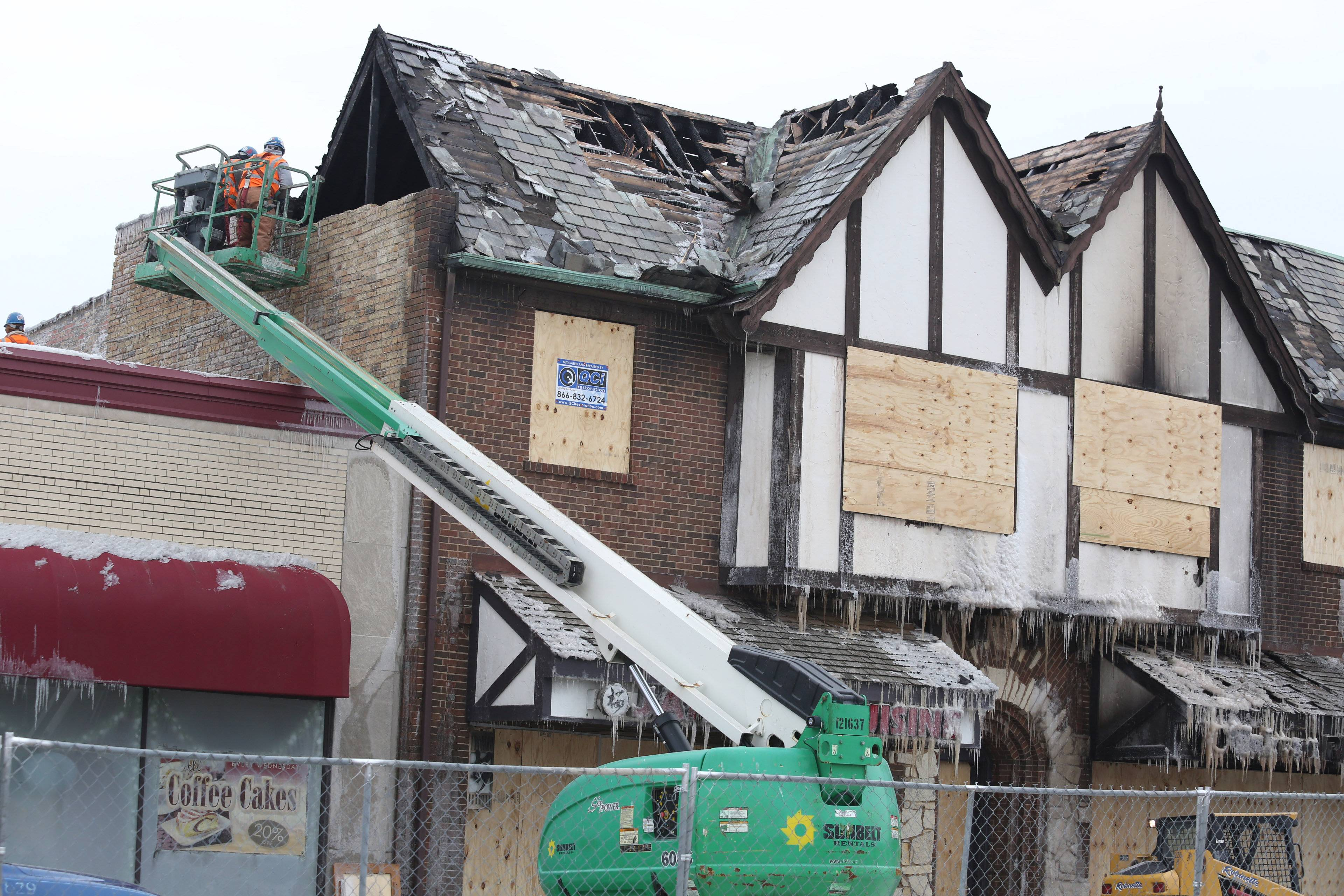 Workers begin to demolish a portion of a building in Mount Prospect Wednesday due to severe damages left by an early Sunday morning fire.
