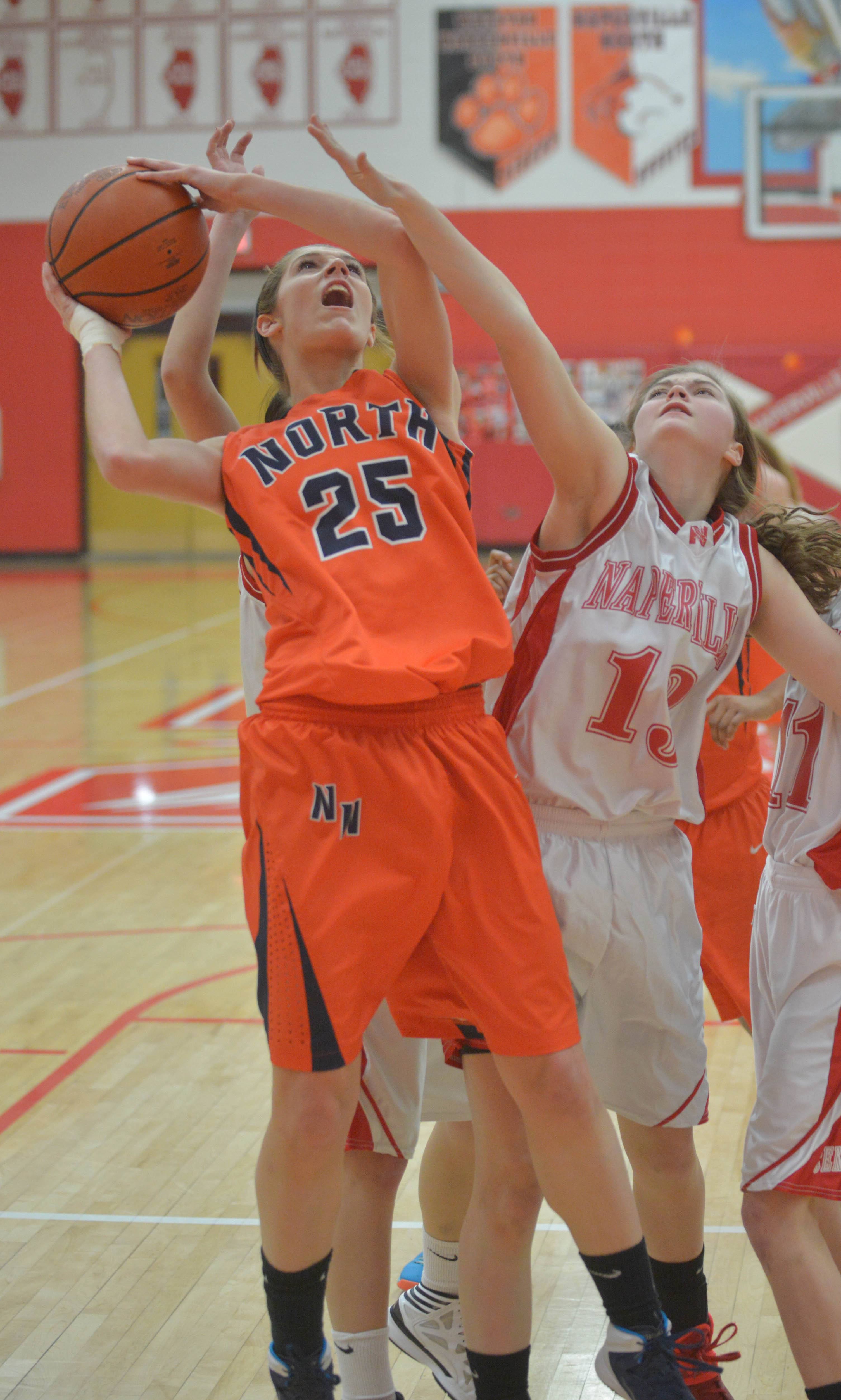 (25) Kayla Sharples of Naperville North and (13) Katie Moran of Naperville Central give it their all during the Naperville North at Naperville Central girls basketball game Thursday.